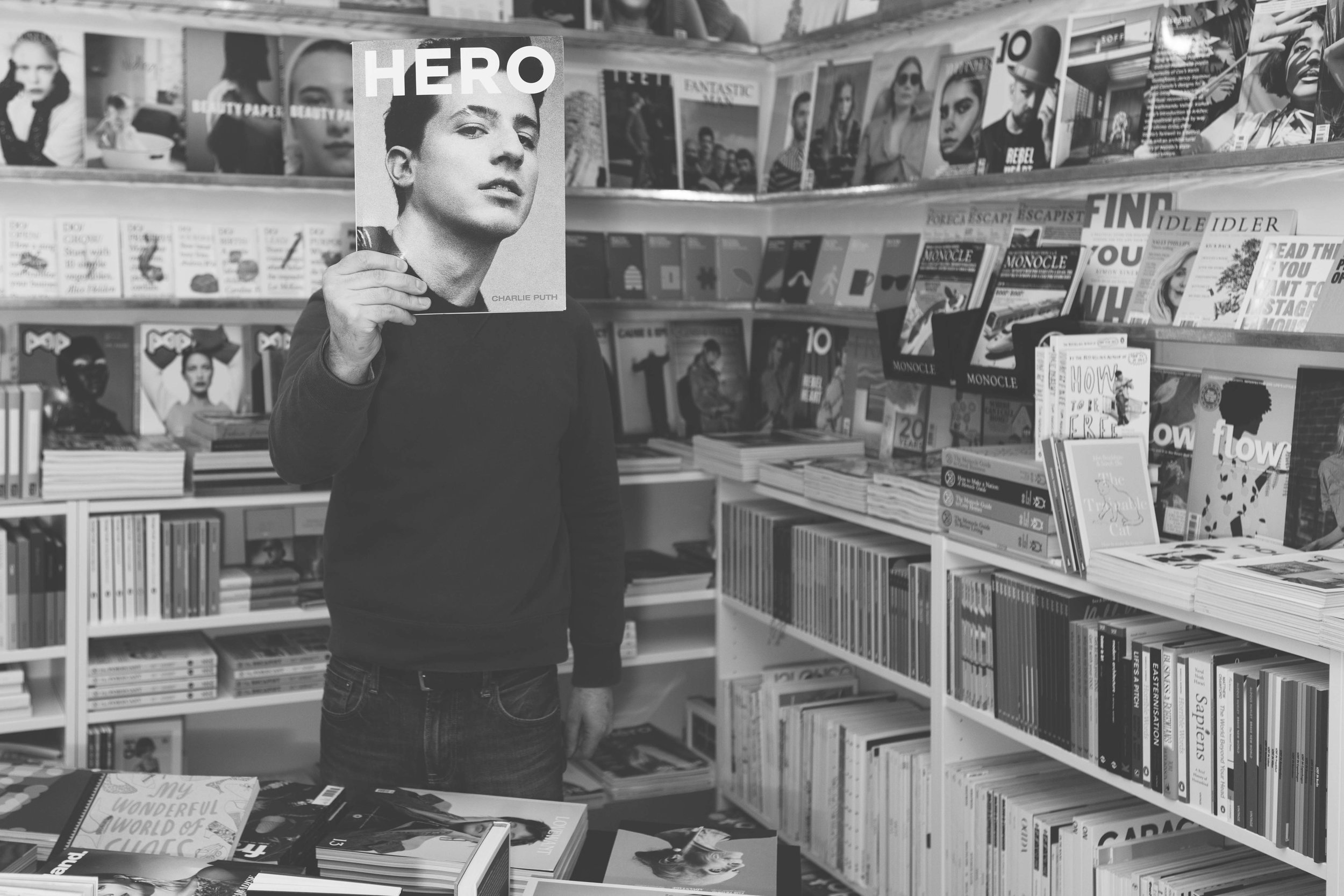 black and white portrait of a man holding a magazine up to his face, with the front cover replacing his face. Surrounded by books either side on white and metal shelves, filled with books and magazines up and down the walls.