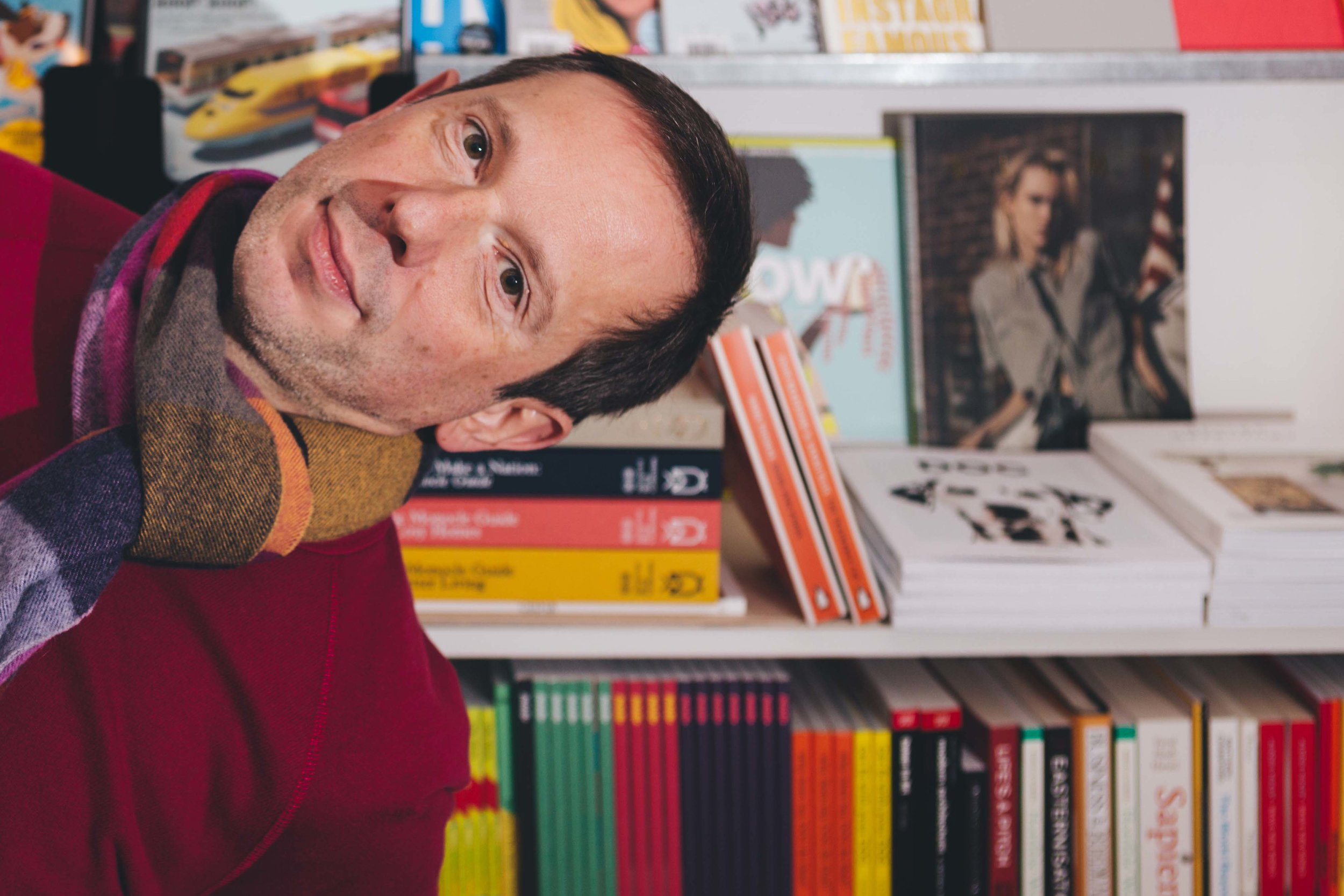 image with bookcases filled with independent magazines and books either side and to the back, with man in red jumper holding more books moving towards camera in a playful way