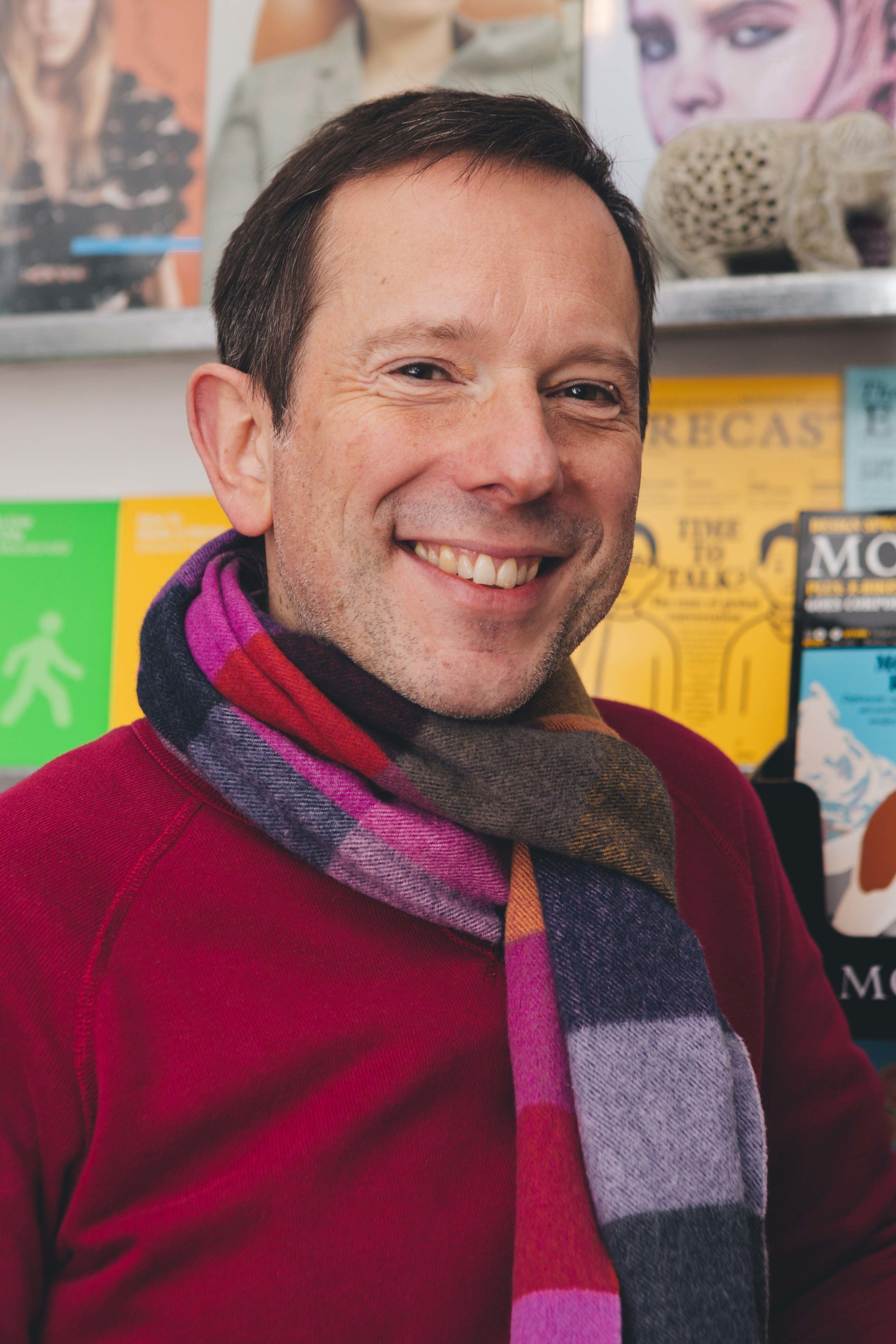 colour portrait image of a man in a red jumper with a striped scarf on smiling to camera, with shelves of books behind him