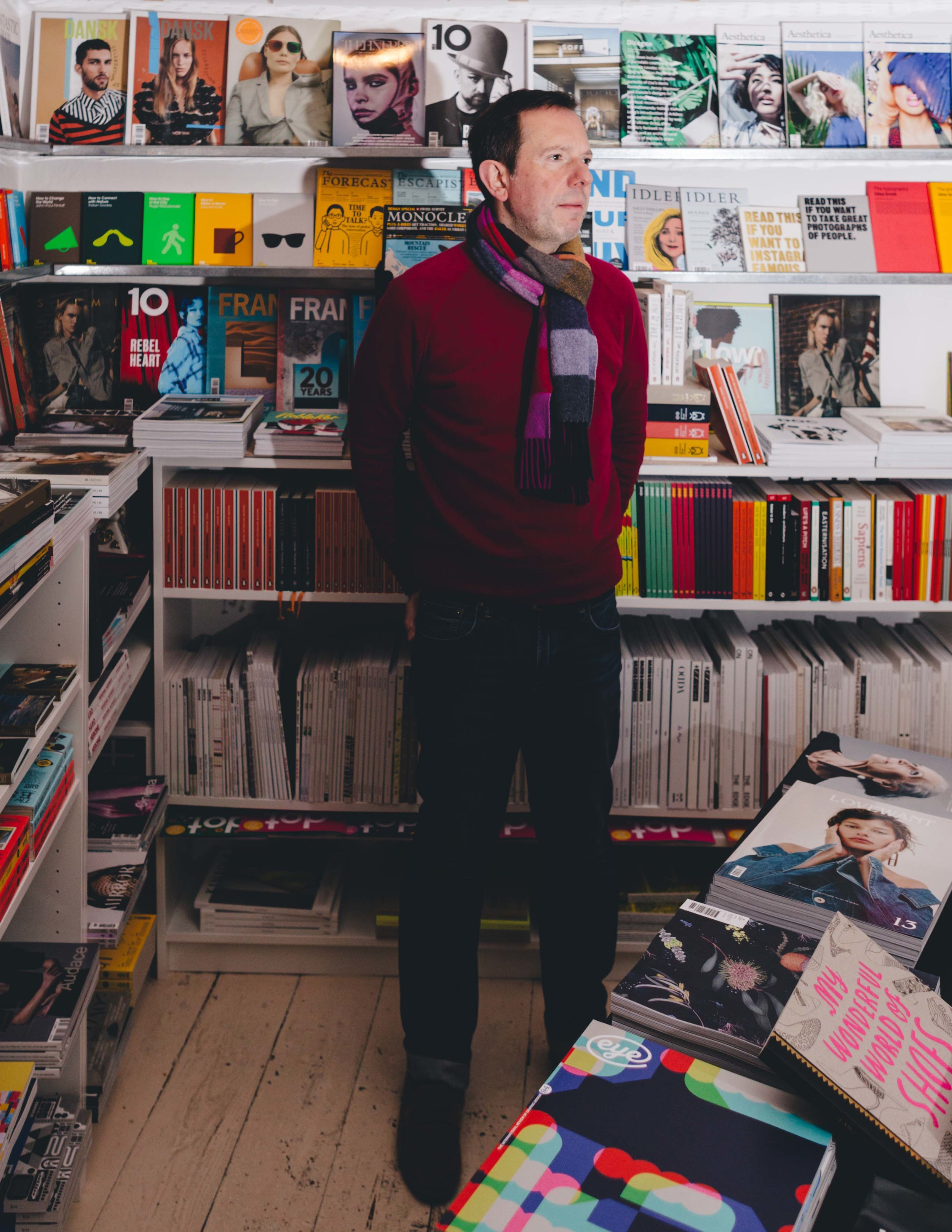 portrait image of a man standing proud looking away from the camera, behind shelves filled with books on the walls down to the floor and books in the forefront