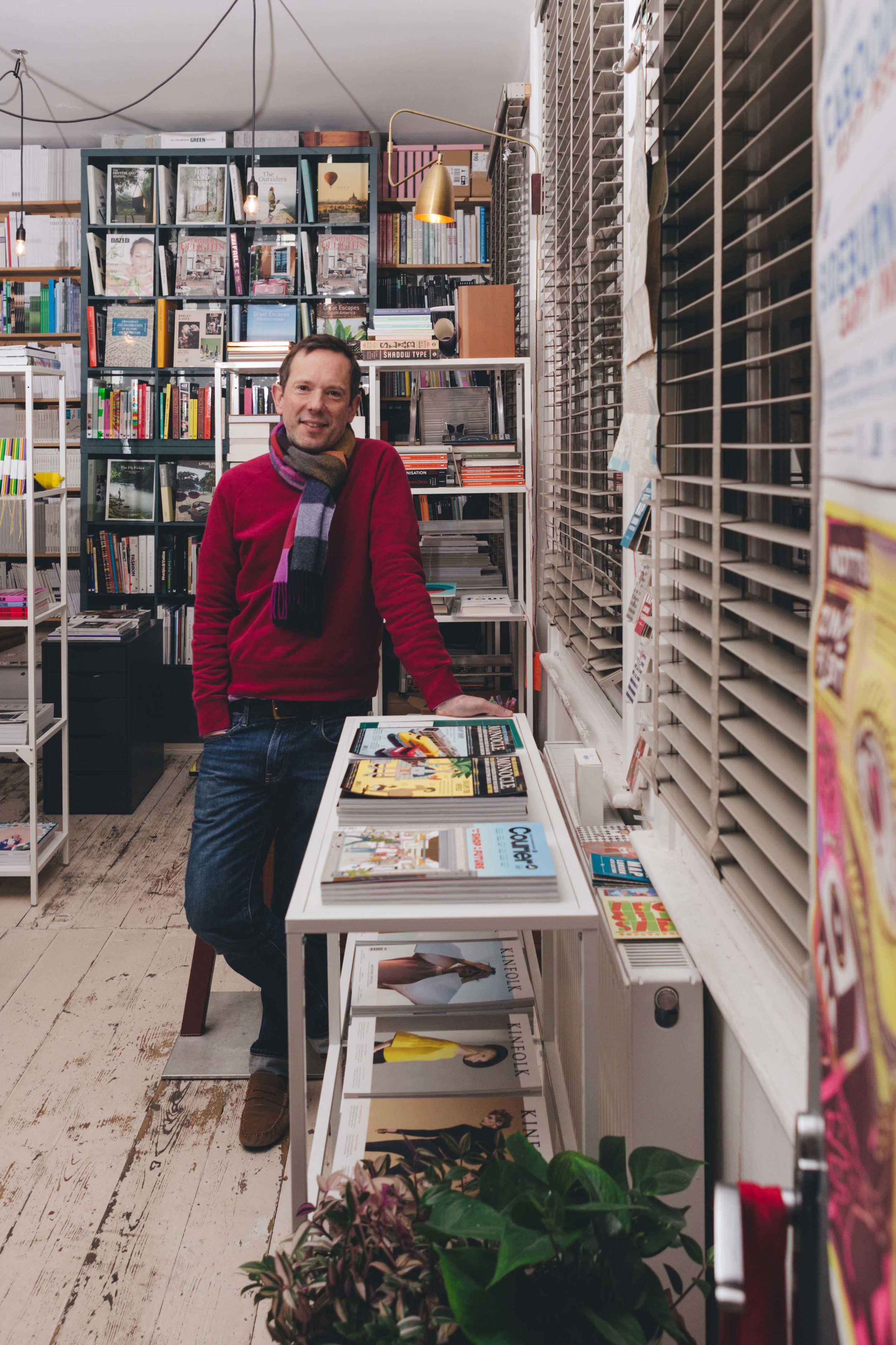 portrait of a man in a book shop with plants in the foreground to the right, blinds also to the right and books in shelves on the walls