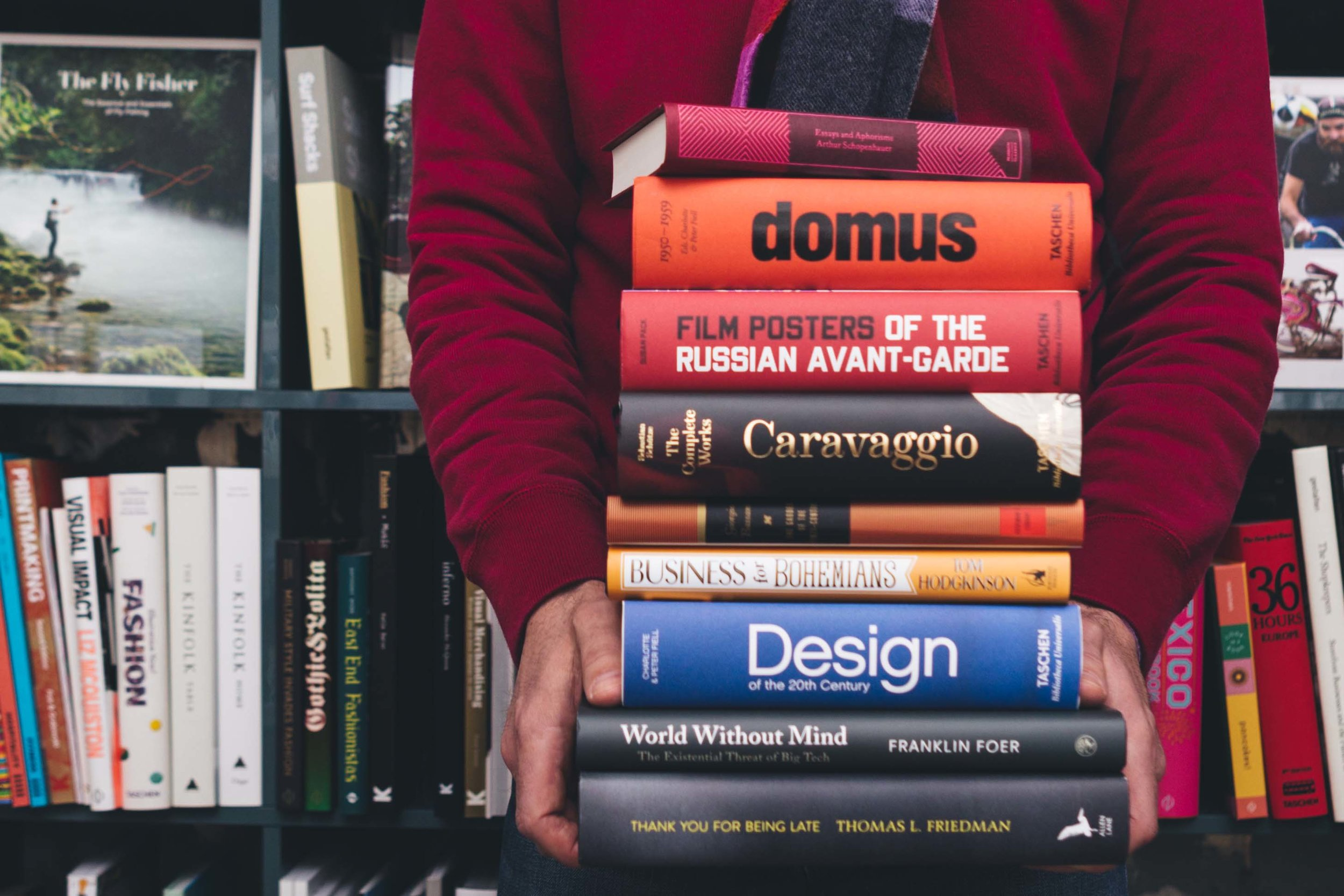 man holding a stack of books, with books behind