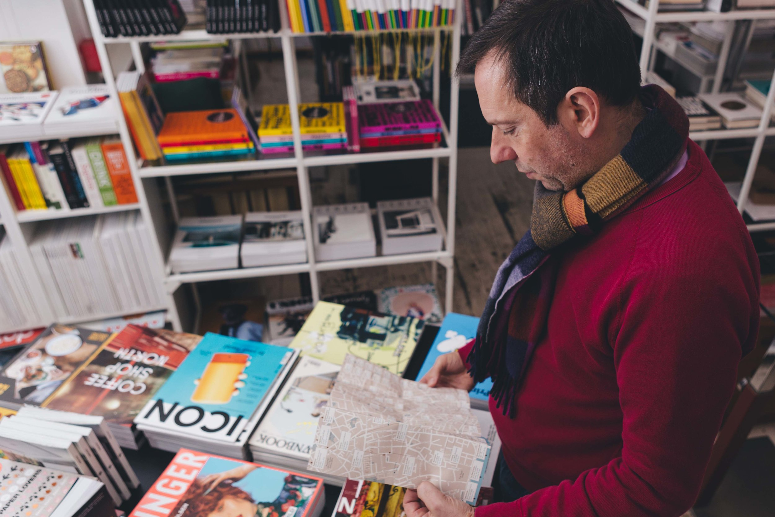book shop filled with colourful books, with man looking at map in the forefront