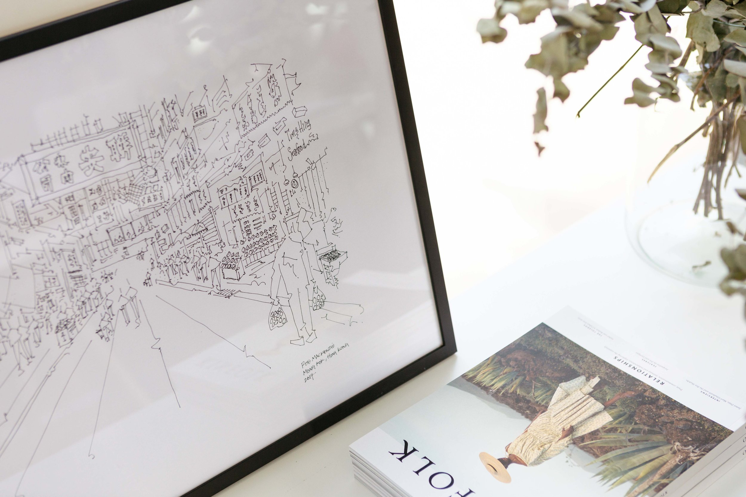Styled product image of hand drawn art with a magazine in the foreground and greenery to the back. Image by Natasha Boyes Photography.