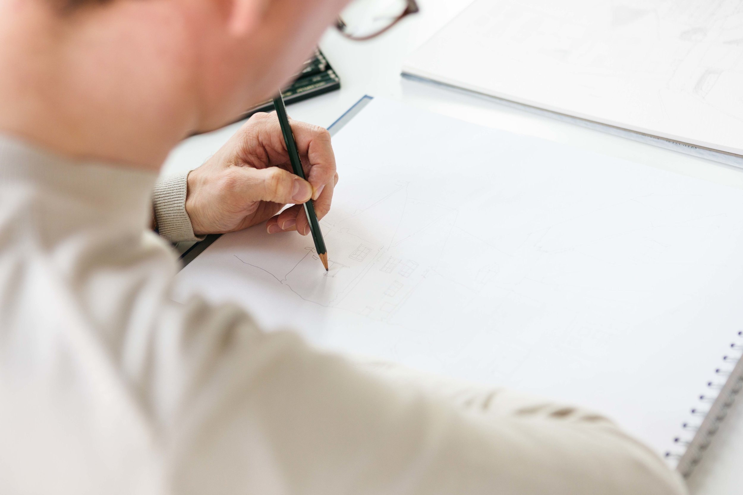 Documentary behind the scenes image of an artist drawing a new piece, on white paper with a pencil. Natasha Boyes Photography