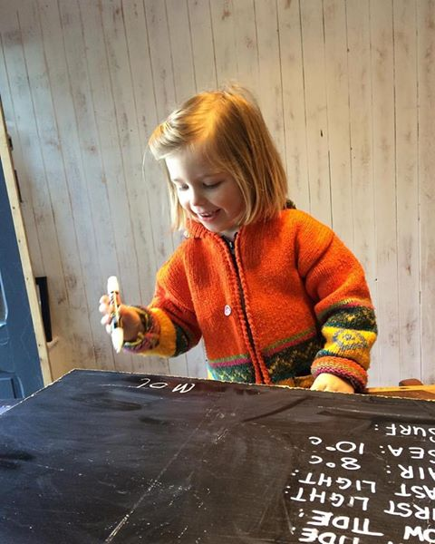 Mollie Mae writing up the surf report for The Green Room Surf School window