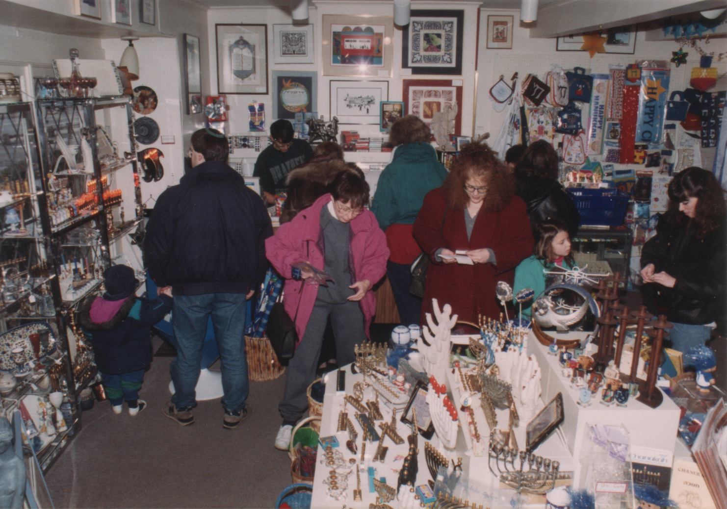 A busy Chanukah in the early 90s at Tradition, with me just vaguely in the back left, in the dark green shirt, manning the cash register.