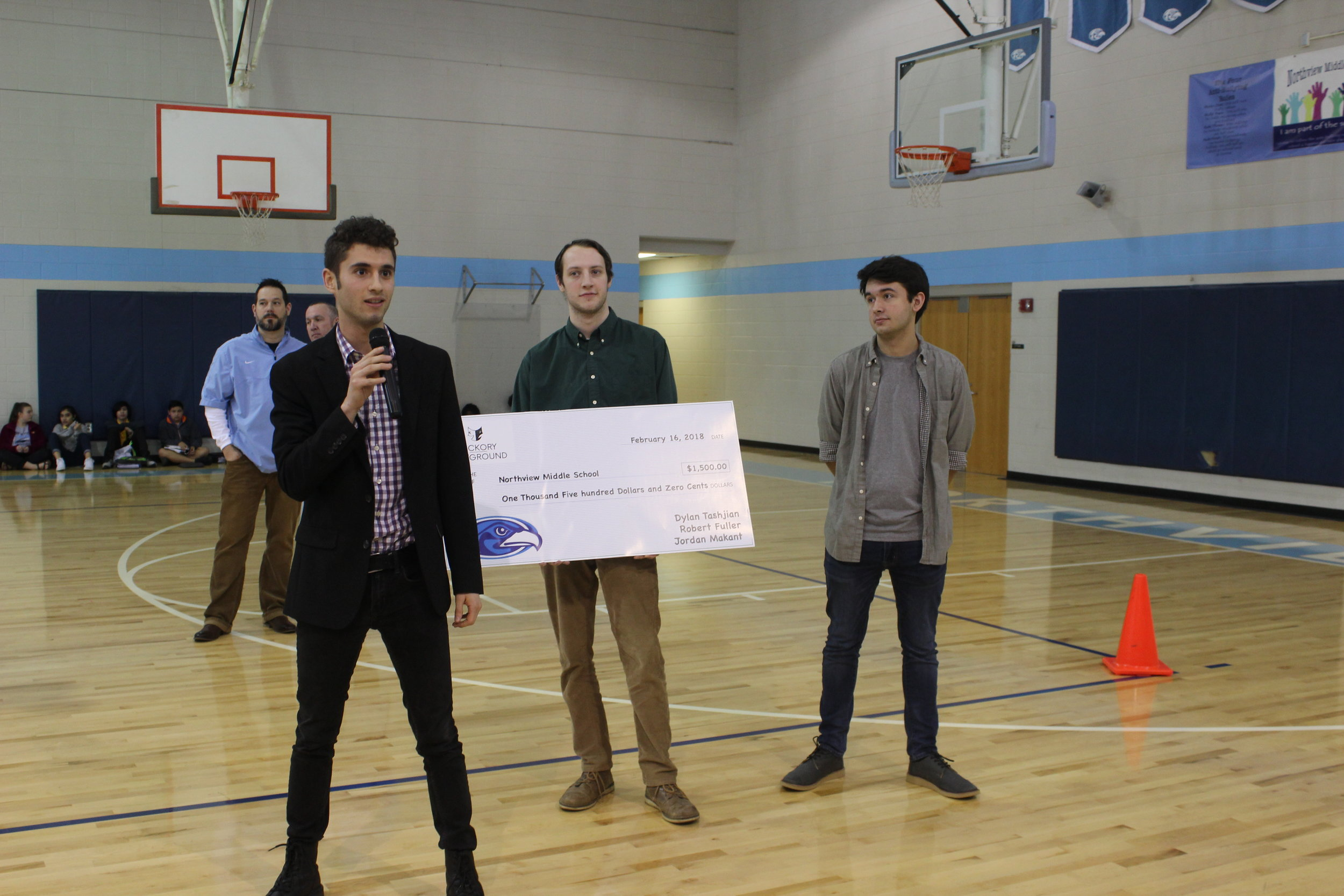 Dylan Tashjian (left), Robert Fuller (center), and Jordan Makant (right) present an oversized check to a school and talk to the students about the importance of the arts in 2017.