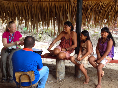 Diana researching book with Amazon Indians and Nat Geo guide in Brazil.