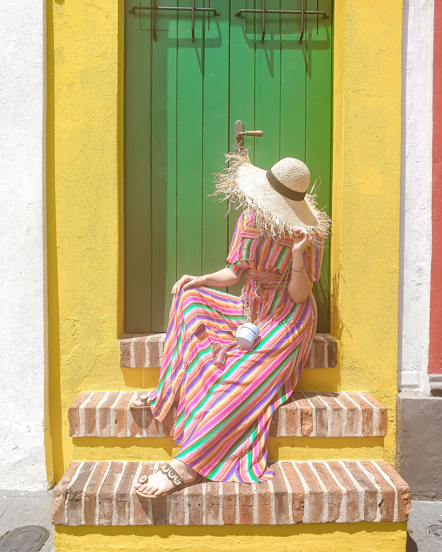Travel Blogger wearing All Things Mochi rainbow dress sitting on stairs in San Juan