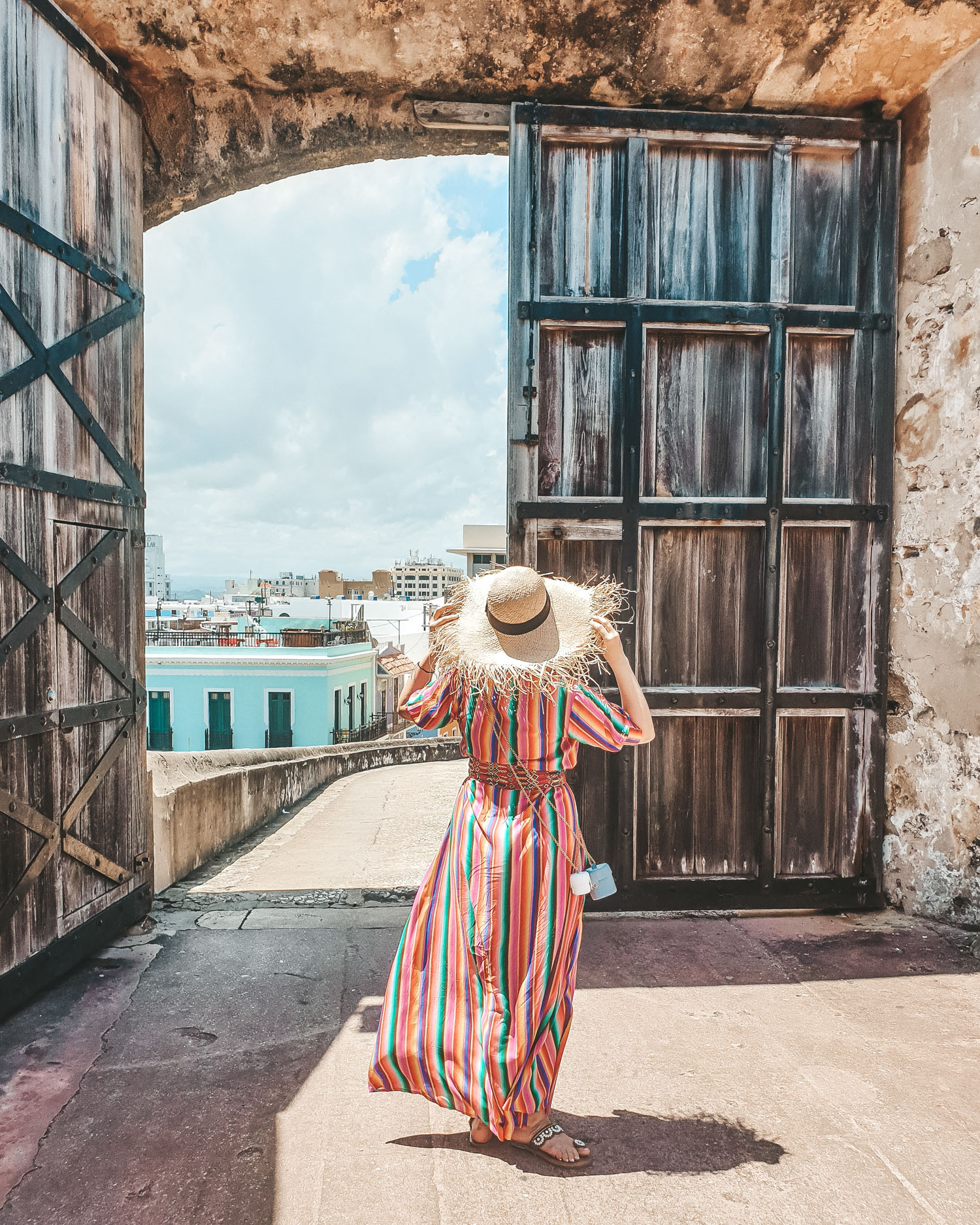 Travel Blogger wearing All Things Mochi rainbow dress posing next to a door