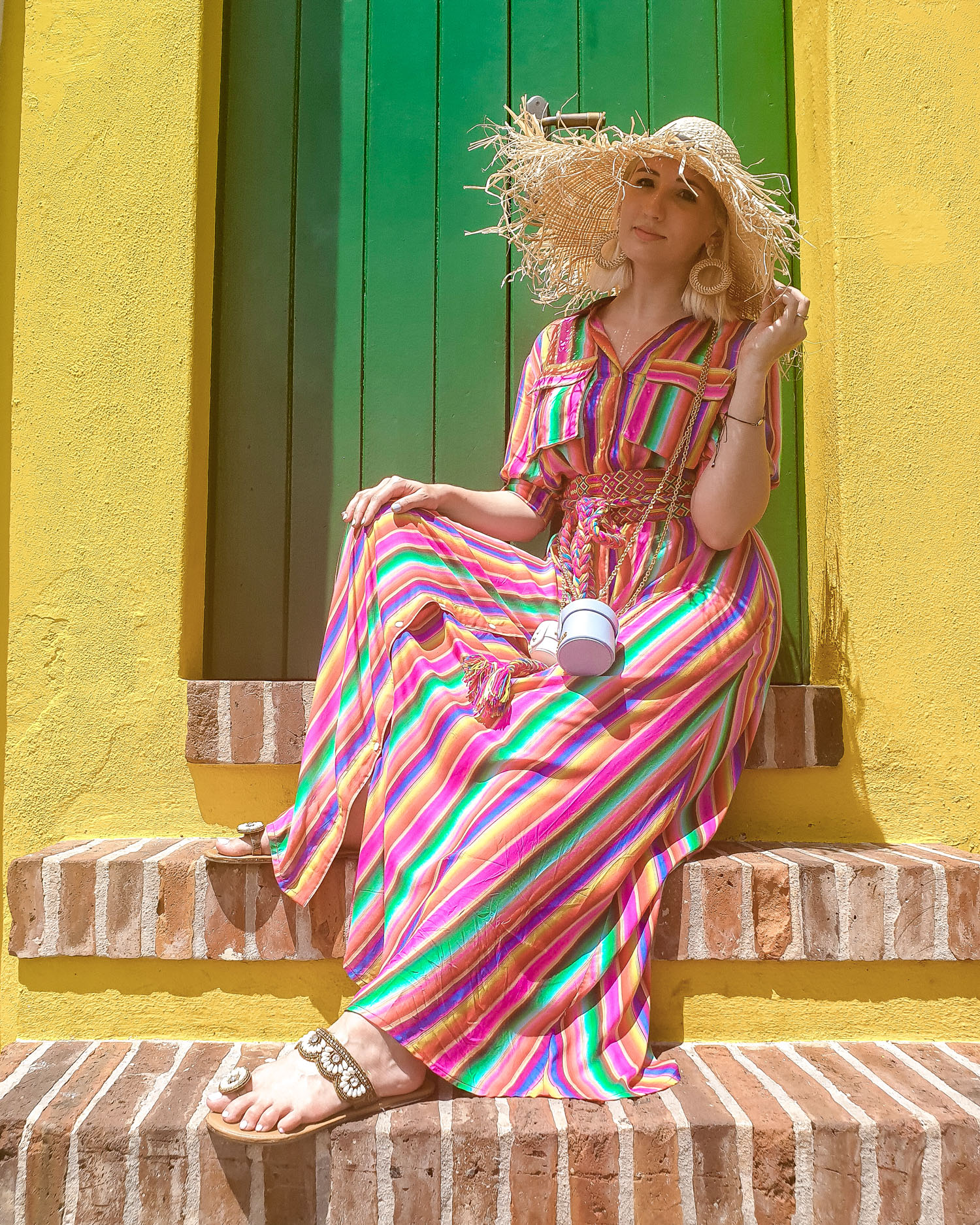 travel blogger wearing All Things Mochi rainbow dress sitting on steps in San Juan, Puerto Rico