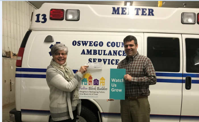 Linda Eagan receives donation from Zach Menter, President and CEO of Oswego County Ambulance Service. This donation makes Menter a NEIGHBORHOOD PRIDE LEADER as a Fulton Block Builder (FBB) Sponsor. Oswego County Ambulance Service, locally known as Menter Ambulance Service, is a private ambulance service whose main headquarters is in Fulton, NY. Their service provides Advanced Life Support emergency ambulance transport, and non-emergent transportation. Zach said he's been watching the changes brought about by the Block Builder program and wanted to become involved. Linda thanks Zach for the very generous donation. Every dollar FBB raises is matched 2-to-1 by the Shineman Foundation up to $100,000.00.