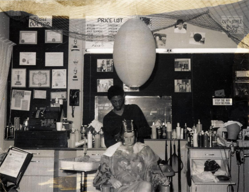 "Nate the Bush Doctor at work in his Deane Avenue shop. c1969-1970. Notice the ""Stop the War, Feed the Poor"" sign. NMAH, SI."