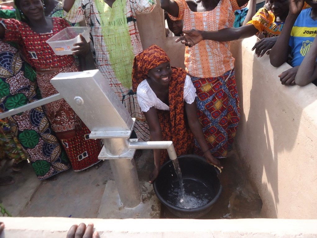 A woman draws clean water for the first time in Ambassana village, in Chad at the well dedication ceremony. Living Water funded its first 3 wells in Chad in December, 2016.