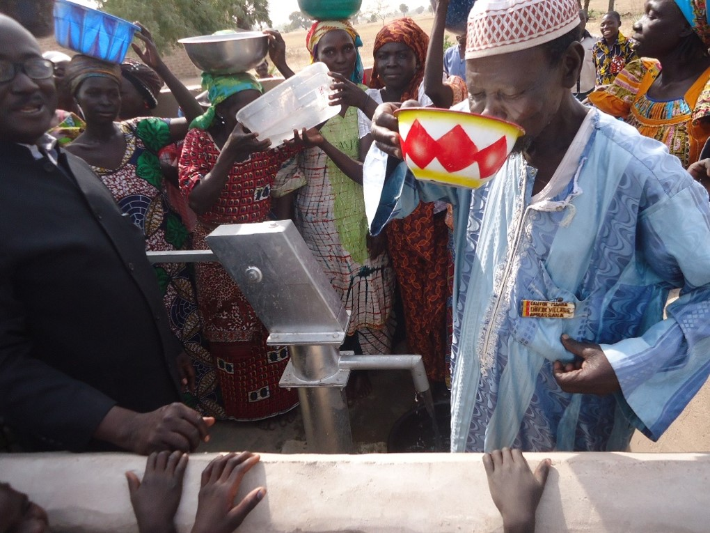 The village chief in Ambassana drinks clean water at the well dedication ceremony. This well is serving 460 people.