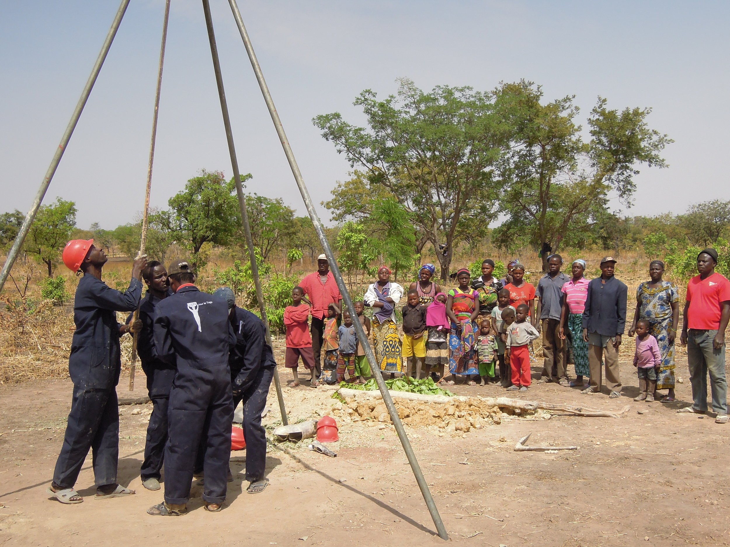 Another drilling team near Kara, Togo. Residence of the village watch in eager anticipation of having clean water for the first time ever.