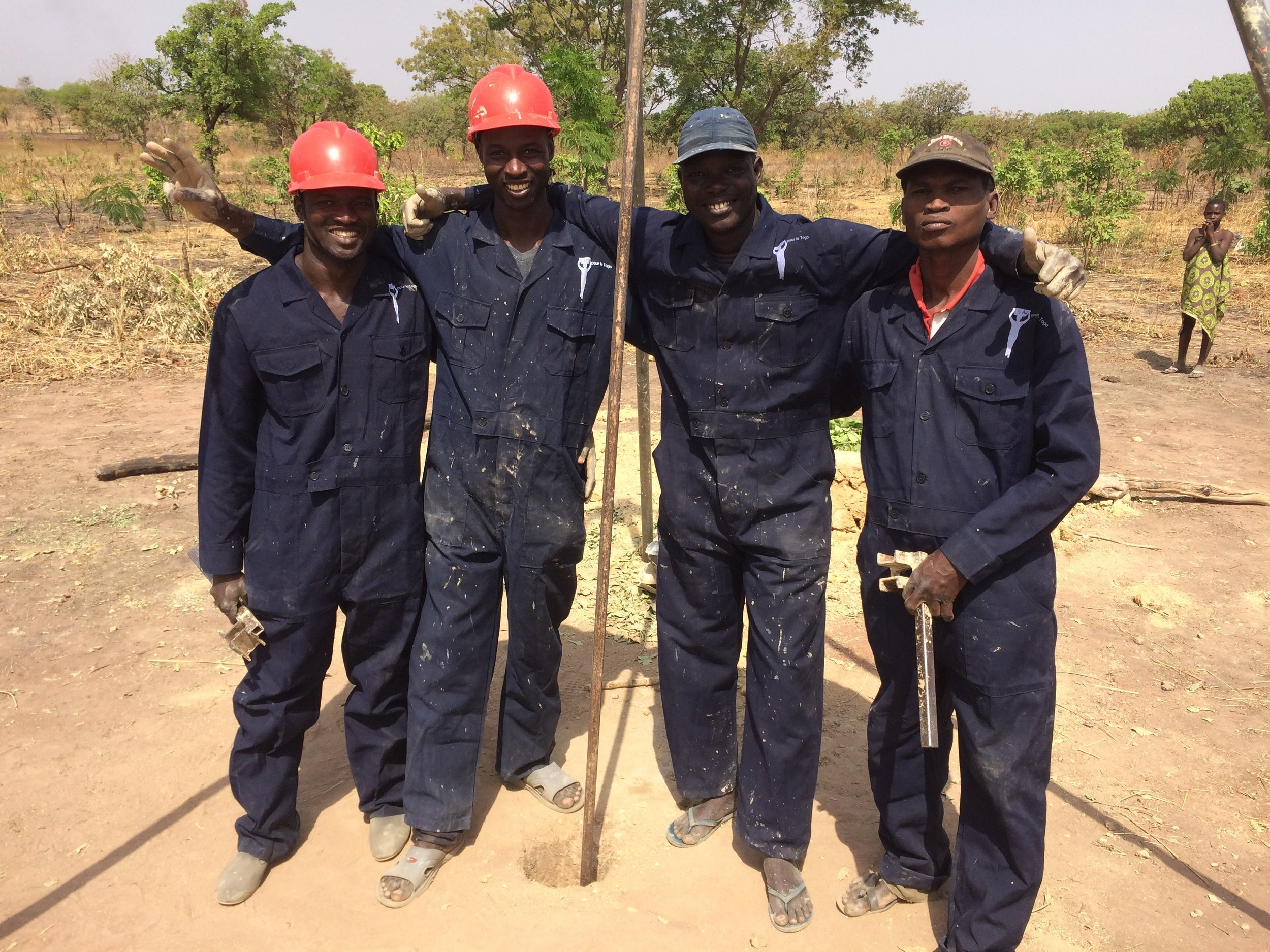 The 4-man drilling team takes a break for a picture. The manual drilling method is much less-expensive than using a large gas-powered drilling rig. These Togo wells cost only $1,600 each!
