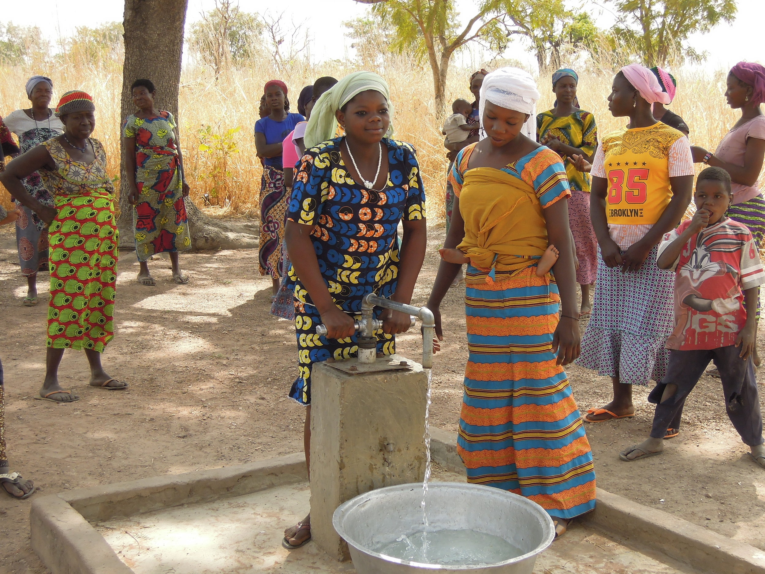 The women enjoyed posing for pictures at the new well. Because a new well eliminates the many hours spent every day going to fetch water from distant sources, girls are able to begin attending school as a result.