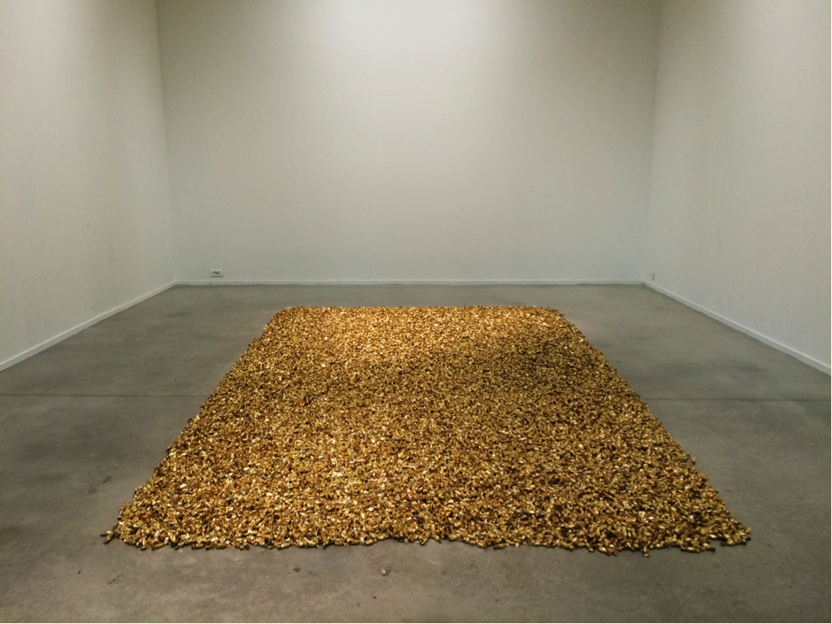 """Félix González-Torres, """"Untitled (Placebo — Landscape — for Roni),"""" 1993. Candies, individually wrapped in gold cellophane, endless supply, Ideal weight: 1,200 lbs., overall dimensions vary with installation."""
