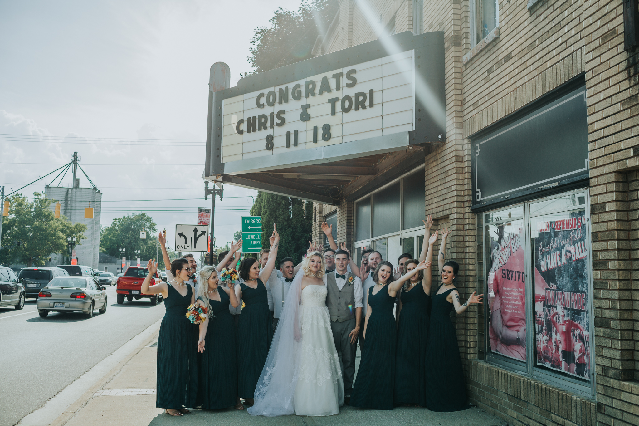 wedding party cheering in front of sign