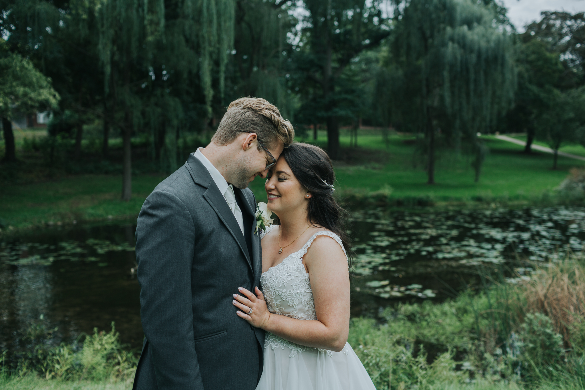 bride and groom in front of a pond