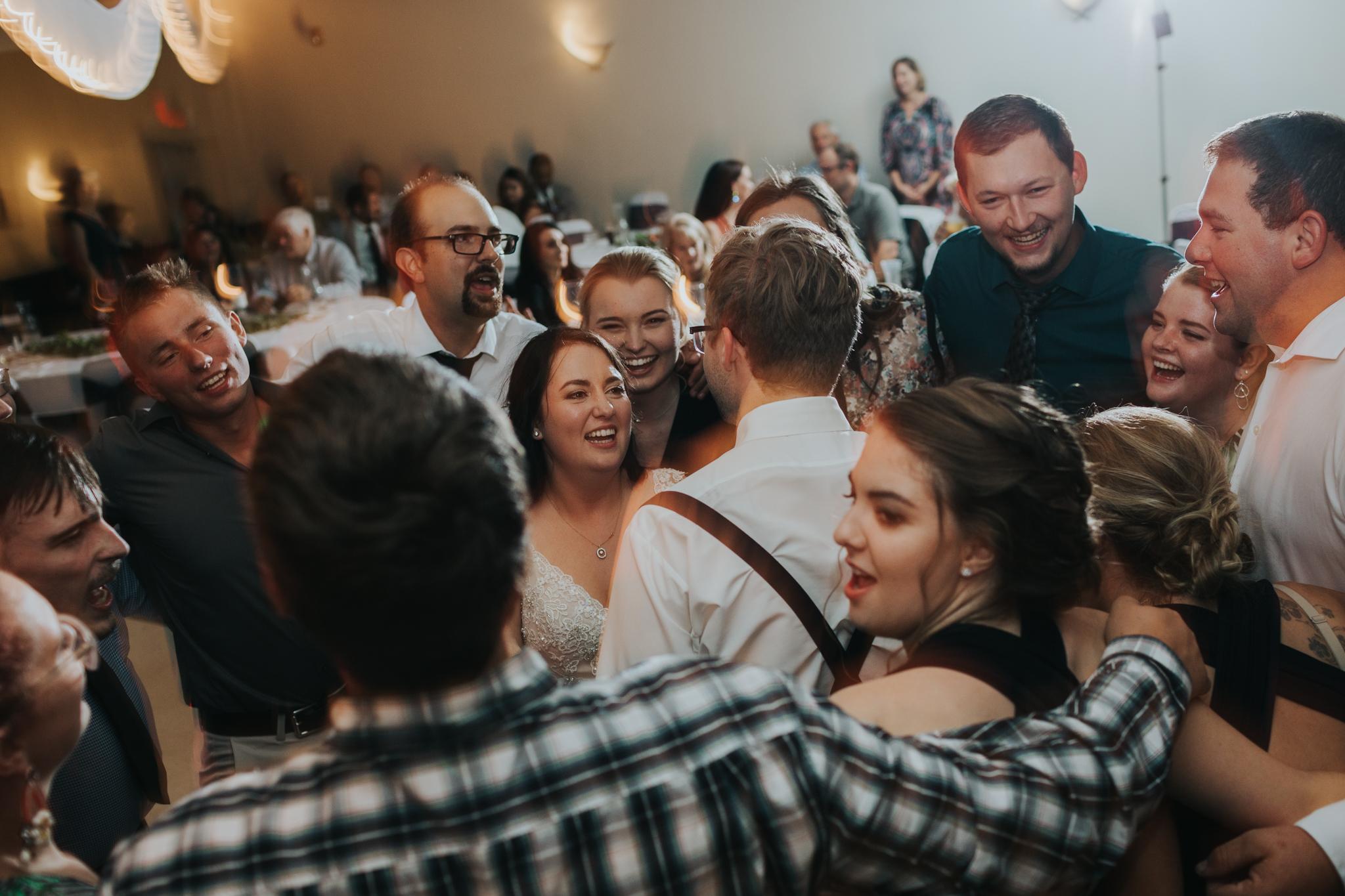 group dancing and singing at wedding reception