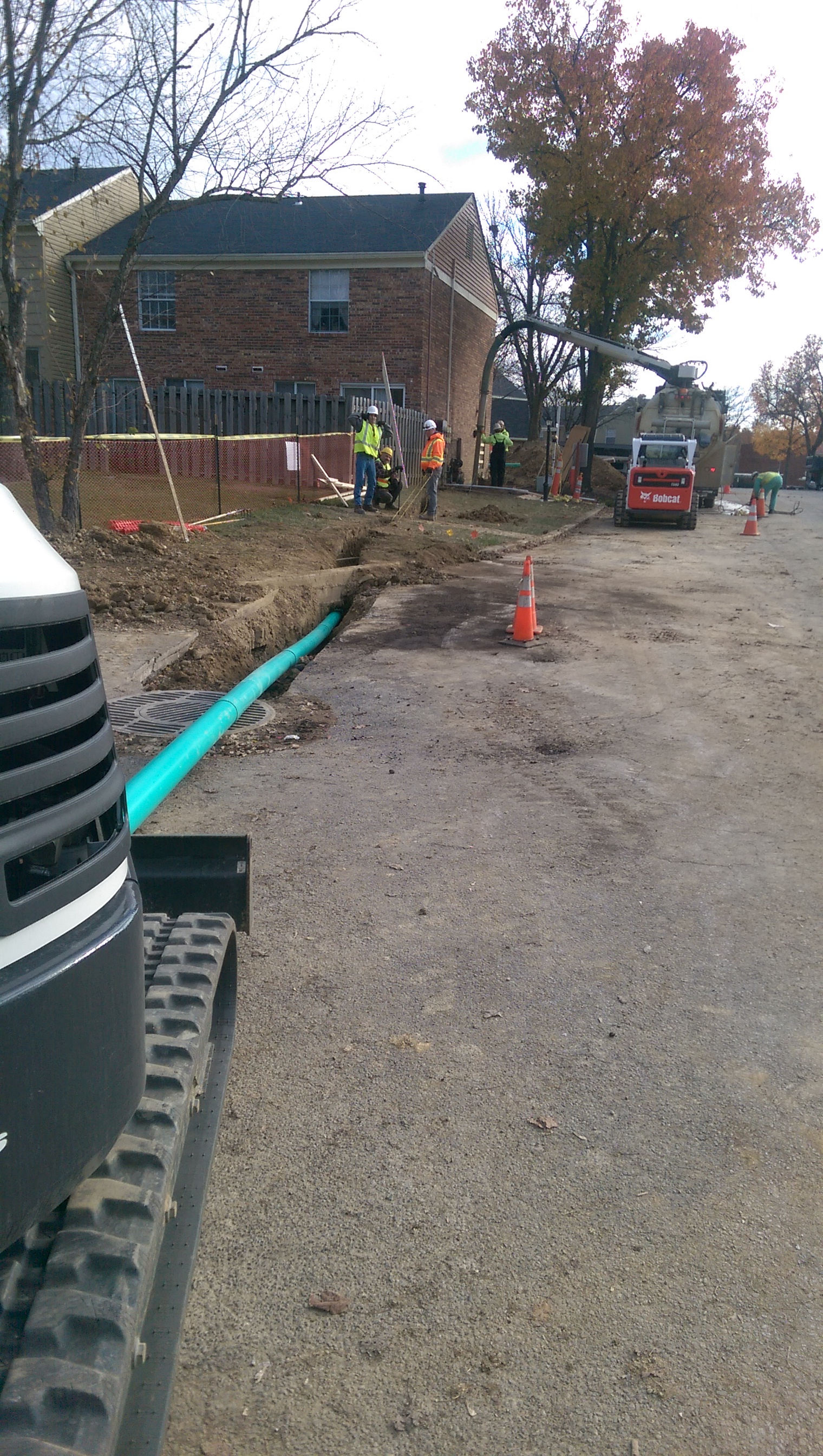 Forcing new drainage under utilities; tie into existing manhole.
