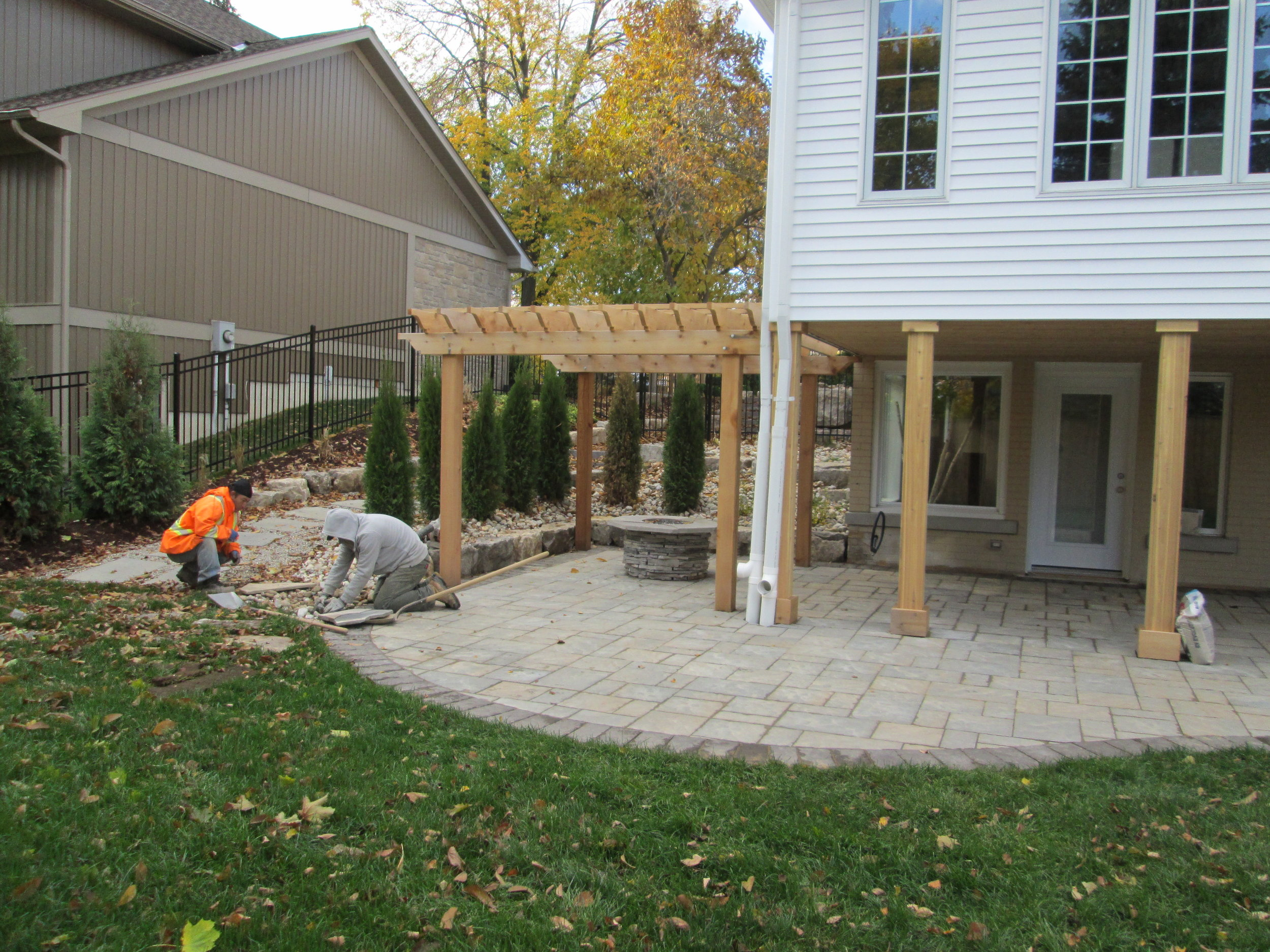 Open area with pergola, and custom fire pit.