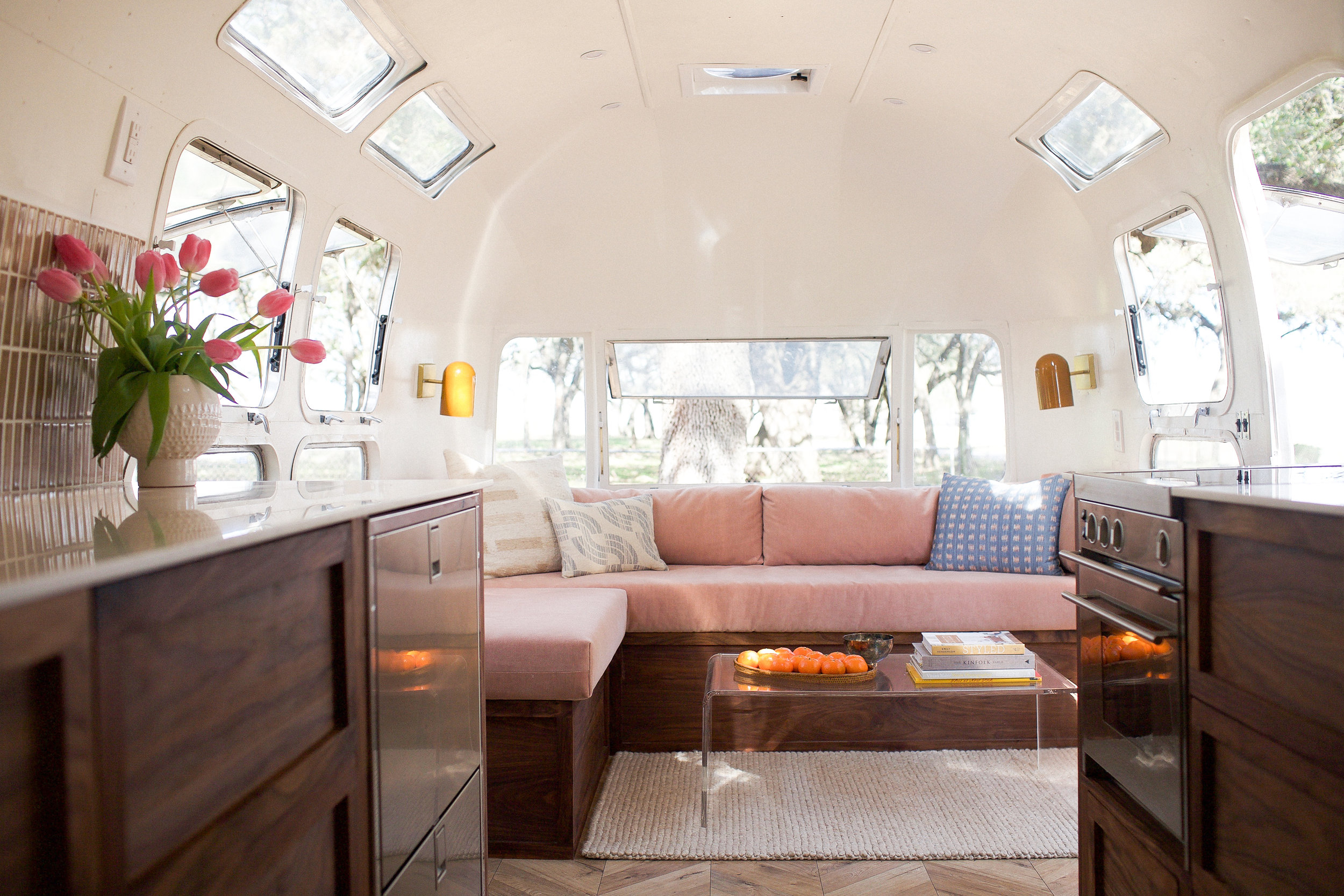 A beautiful airstream with soft pink furnishings and dark wood kitchen