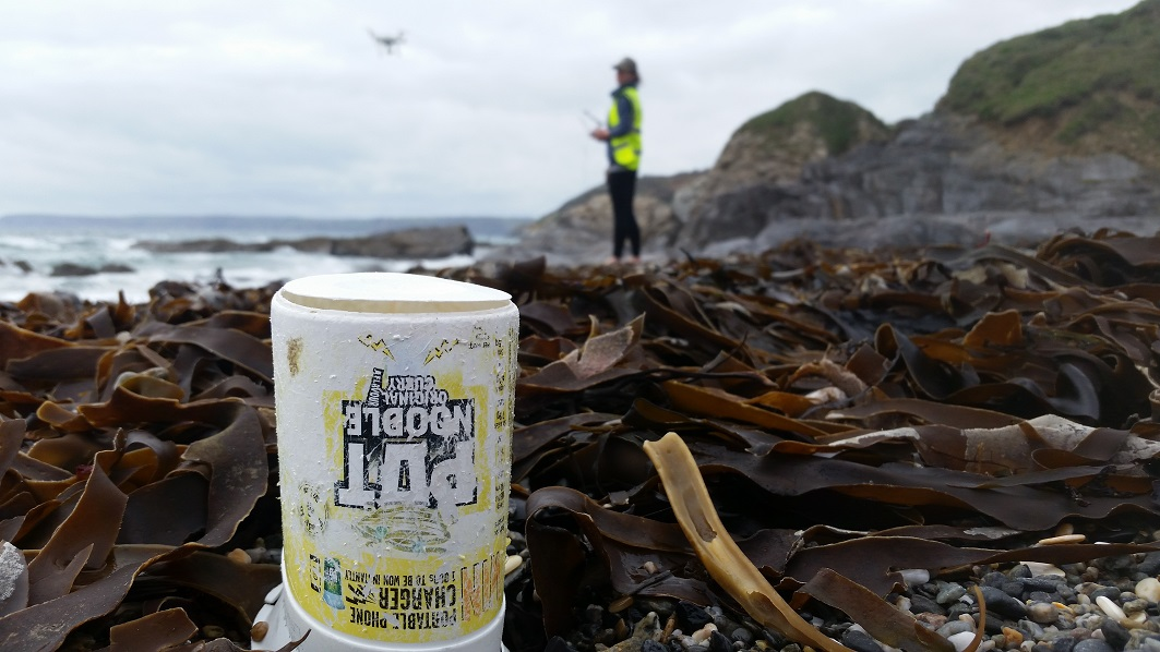 Drone Pilot and Mission Director passing a lonely pot noodle on Hemmick Beach, Cornwall.