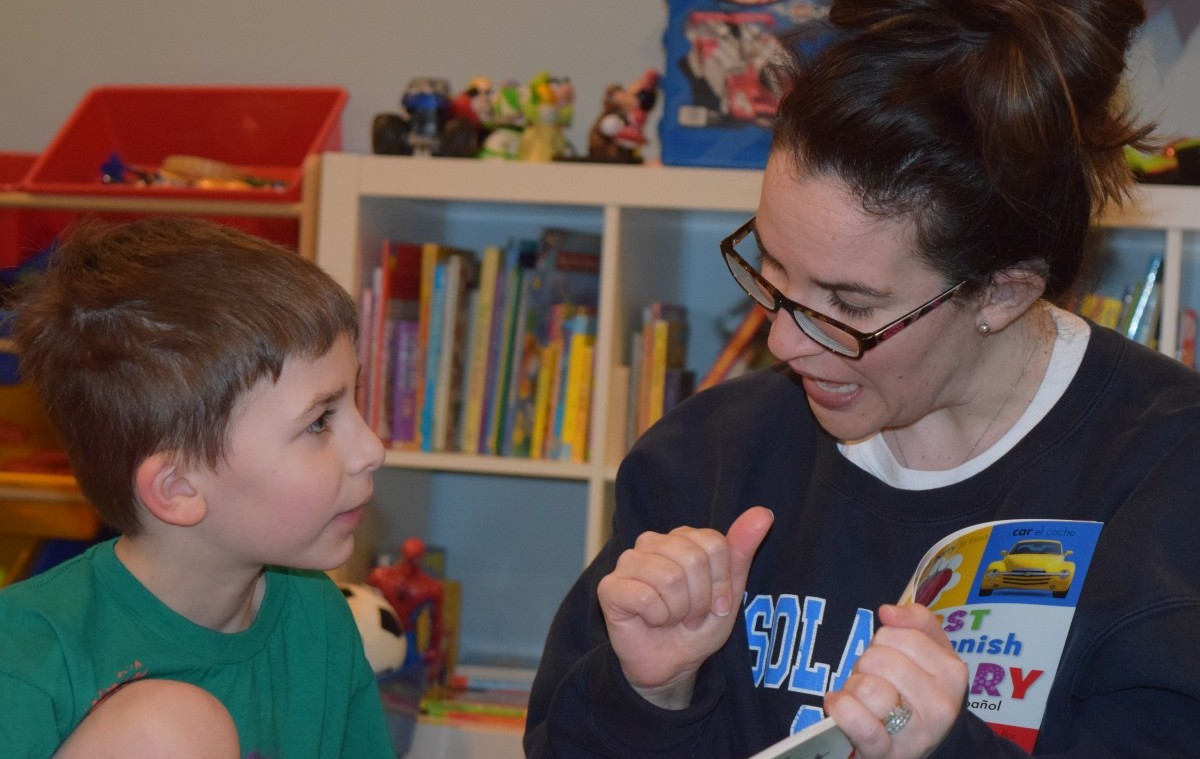 Angela Laguardia (right), who is Deaf, teaches her son Spanish. (Photo by Renee Gross)