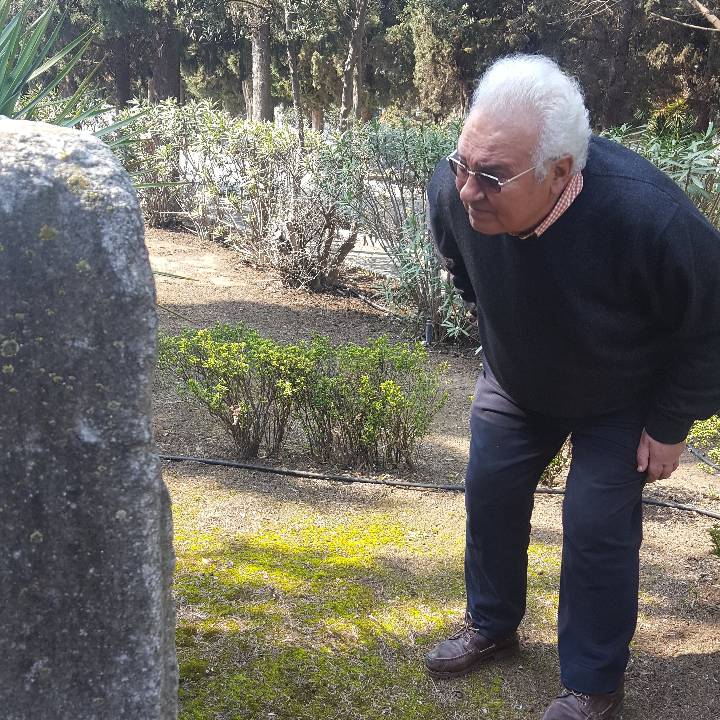 Jacky Benmayor stoops down to get a better look at an old tombstone at the newer Jewish cemetery. (Photo by Renee Gross)