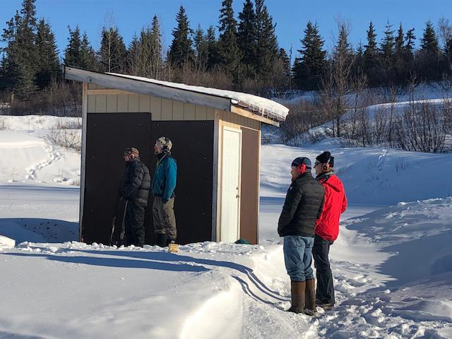 Men wait their turn to shoot at the Kachemak Gun Club and Range. (Photo by Renee Gross)