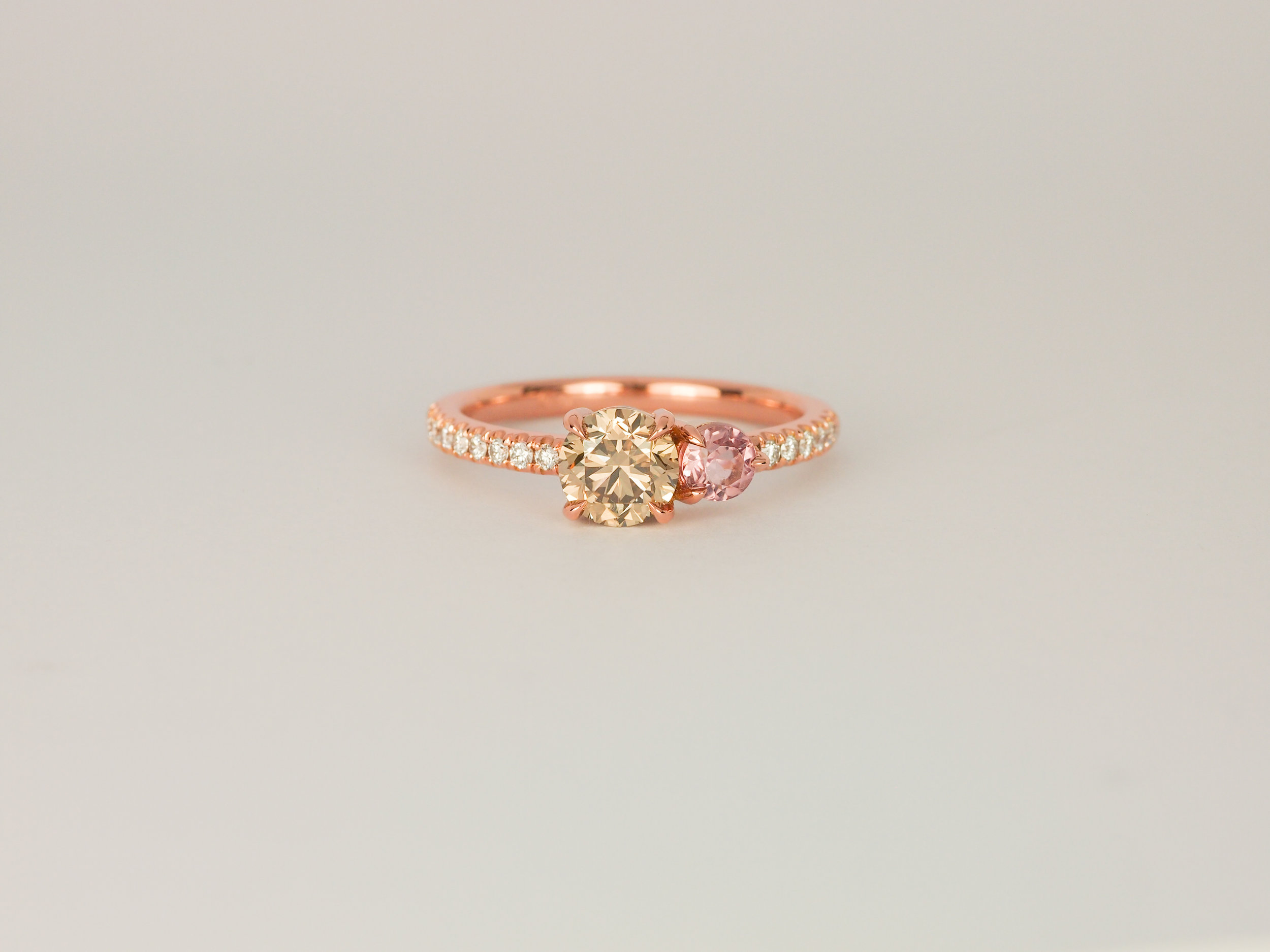 Champagne diamond and pink tourmaline rose gold engagement ring with a thin band of diamonds