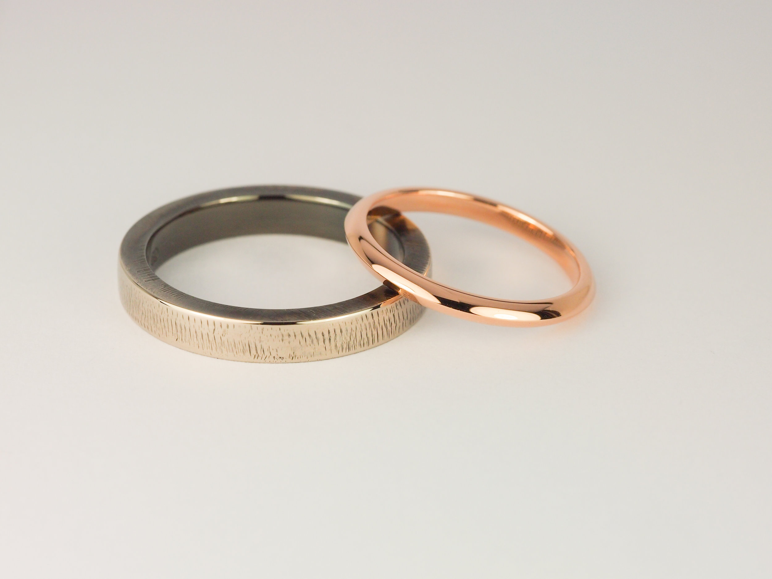 Men's grey white gold and black rhodium ring and ladies knife edge band in rose gold