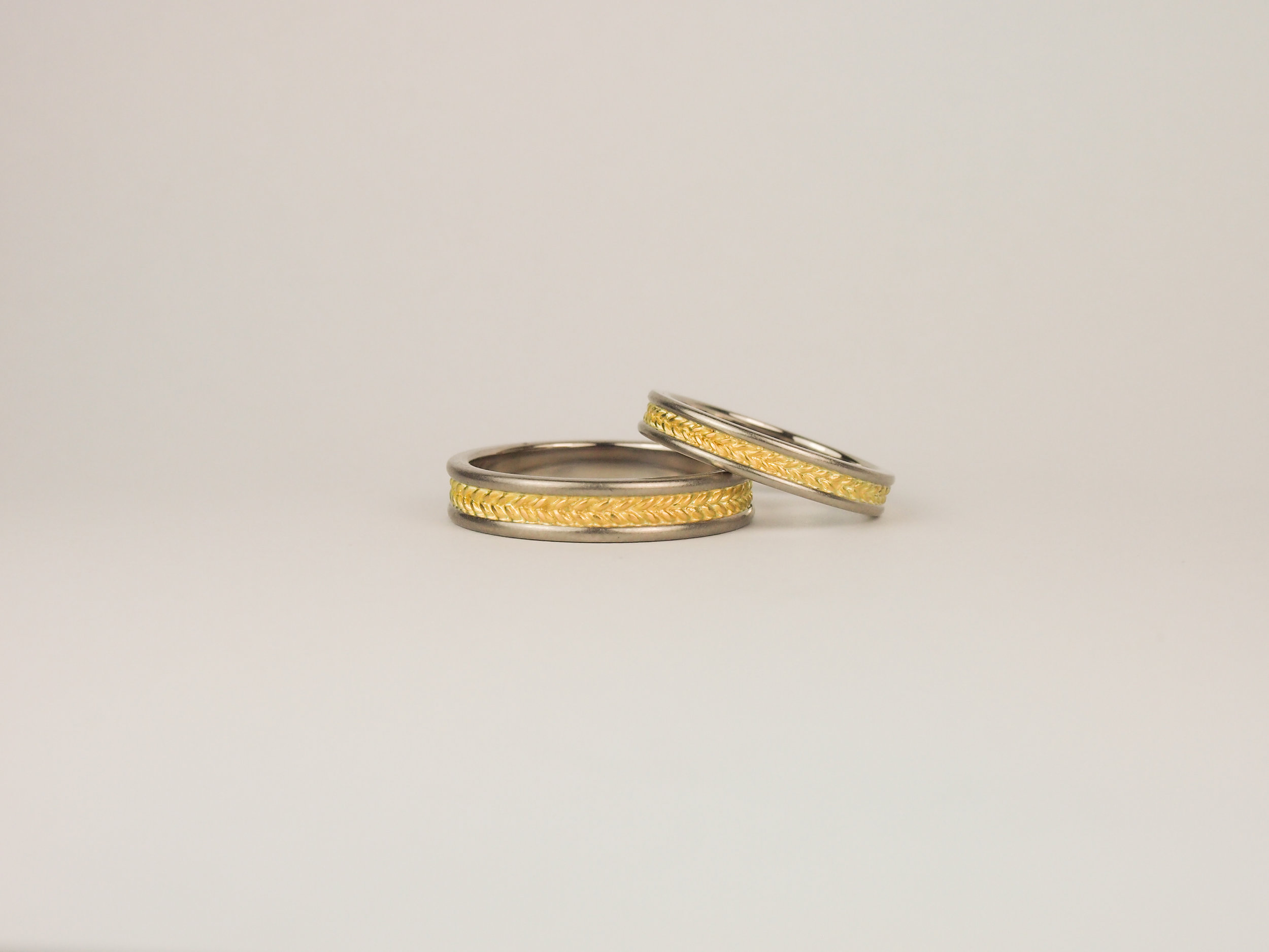 Matching twist pattern wedding rings in yellow and grey white gold