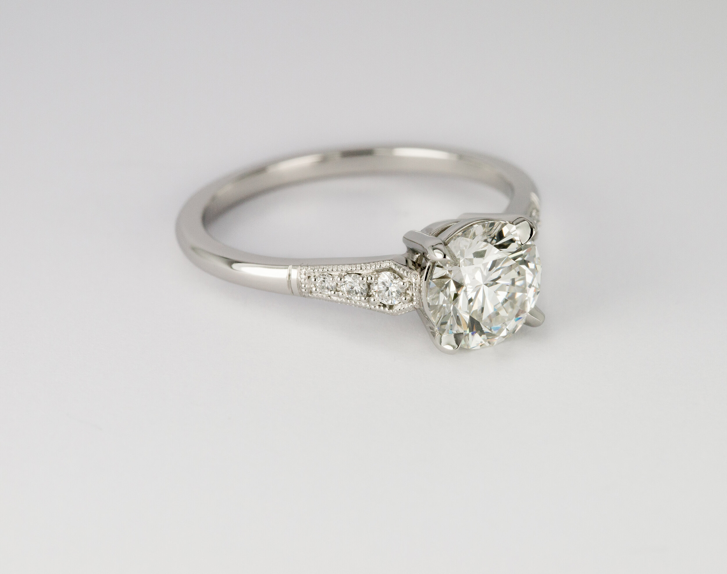 Platinum diamond engagement ring with millegrain detail.