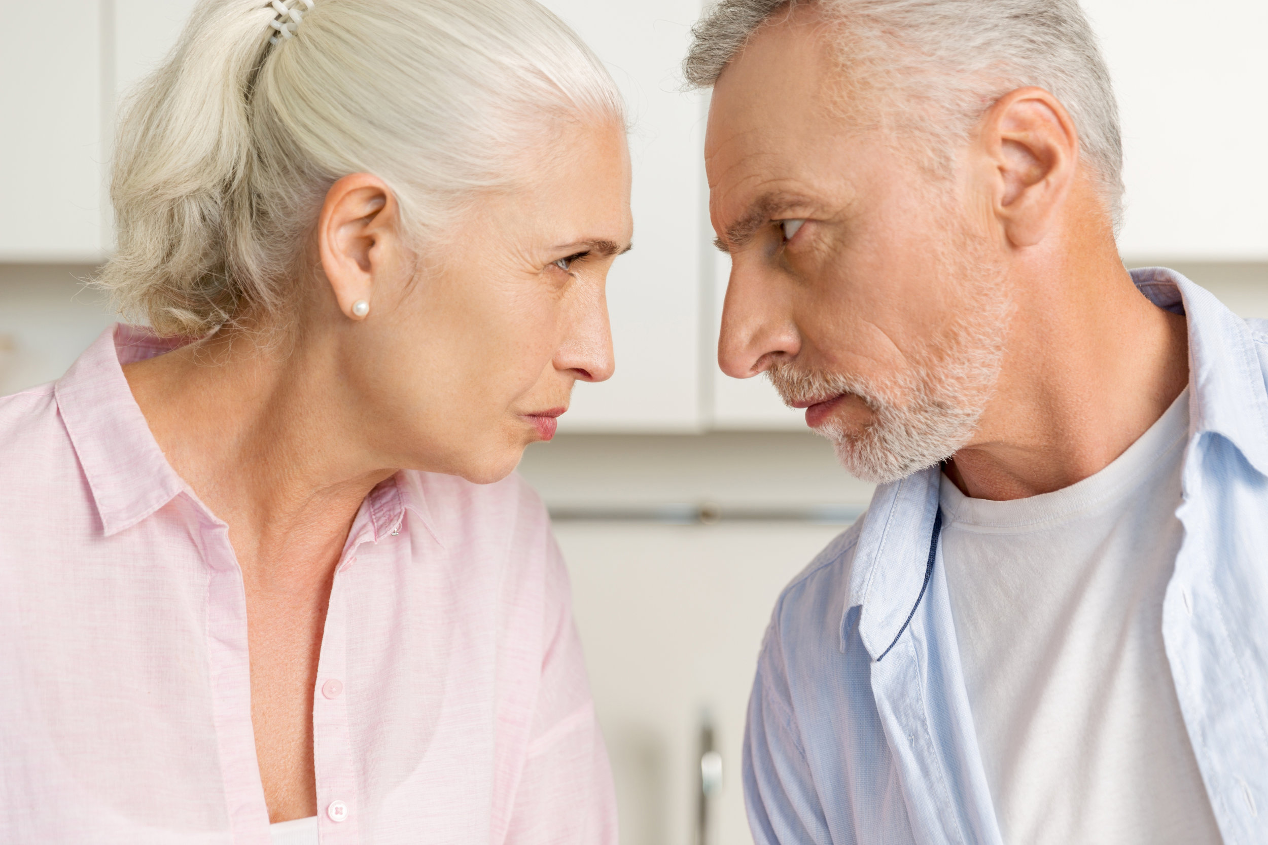 storyblocks-image-of-angry-mature-man-standing-near-mature-serious-woman-at-the-kitchen-looking-at-each-other_S0gGkH3pcZ.jpg
