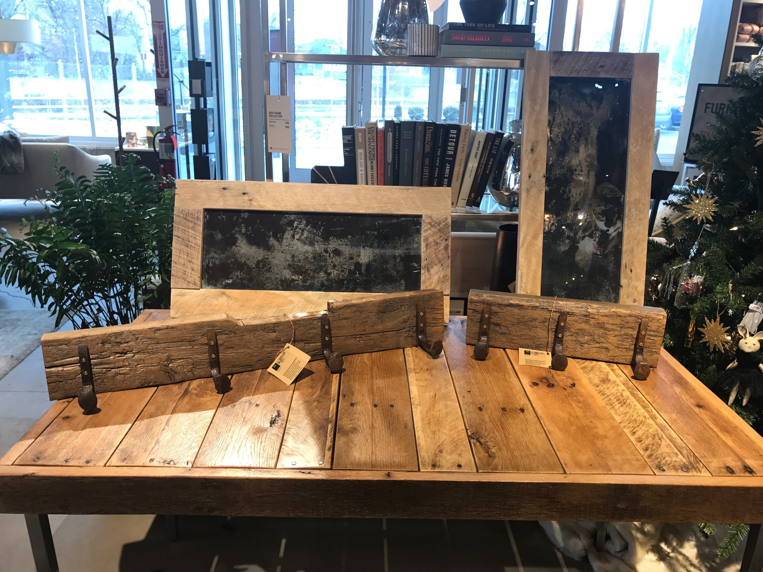 Reclaimed wood table on salvaged chrome legs, railroad spike coat racks and vintage style mirrors with rustic reclaimed wood frames.