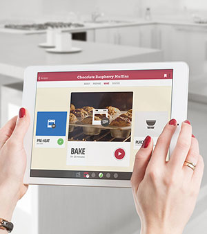 Woman using the Drop Recipes app to control her GE Appliances oven