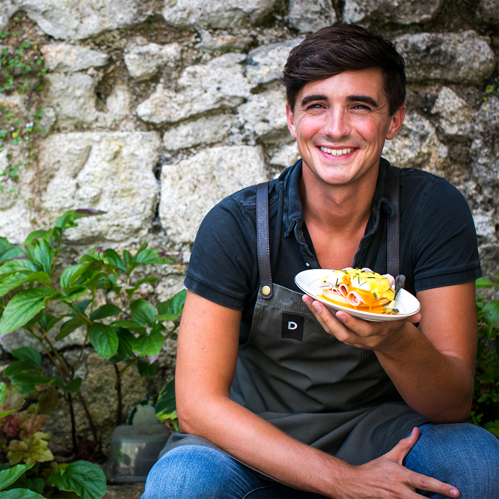 Donal Skehan sitting down and smiling, holding a plate of food