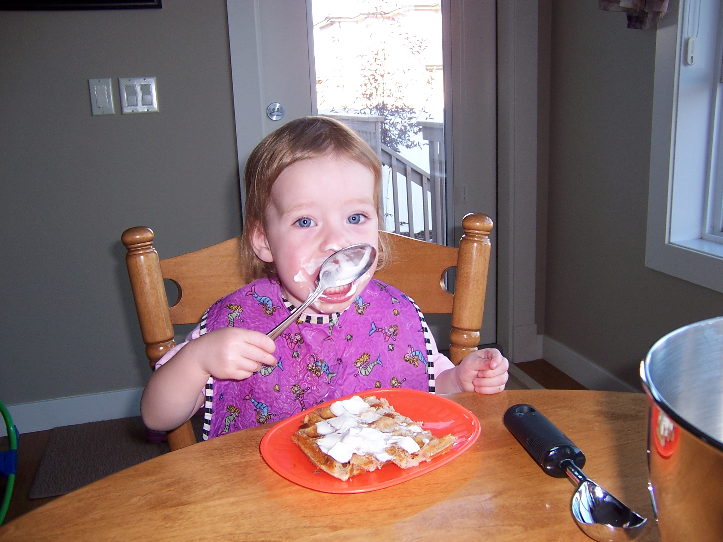 A pic of my daughter who had severe milk and egg allergies, eating her favorite egg and milk free waffles with coconut whip.