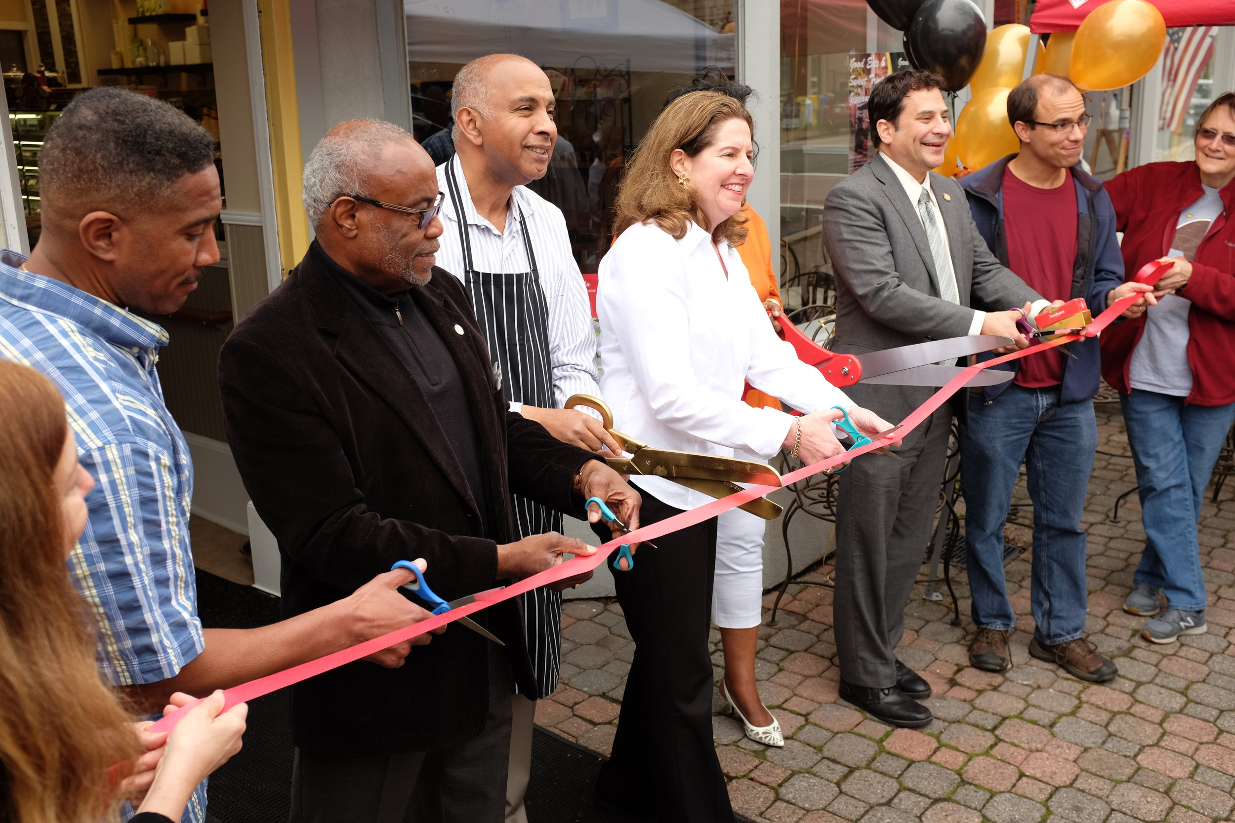 The Mayor of Alexandria, Allison Silberberg, leads the ribbon-cutting for Dolce and Bean, a new business on the Avenue selling premium confections, gelato, and coffee. I spend far too much time there.