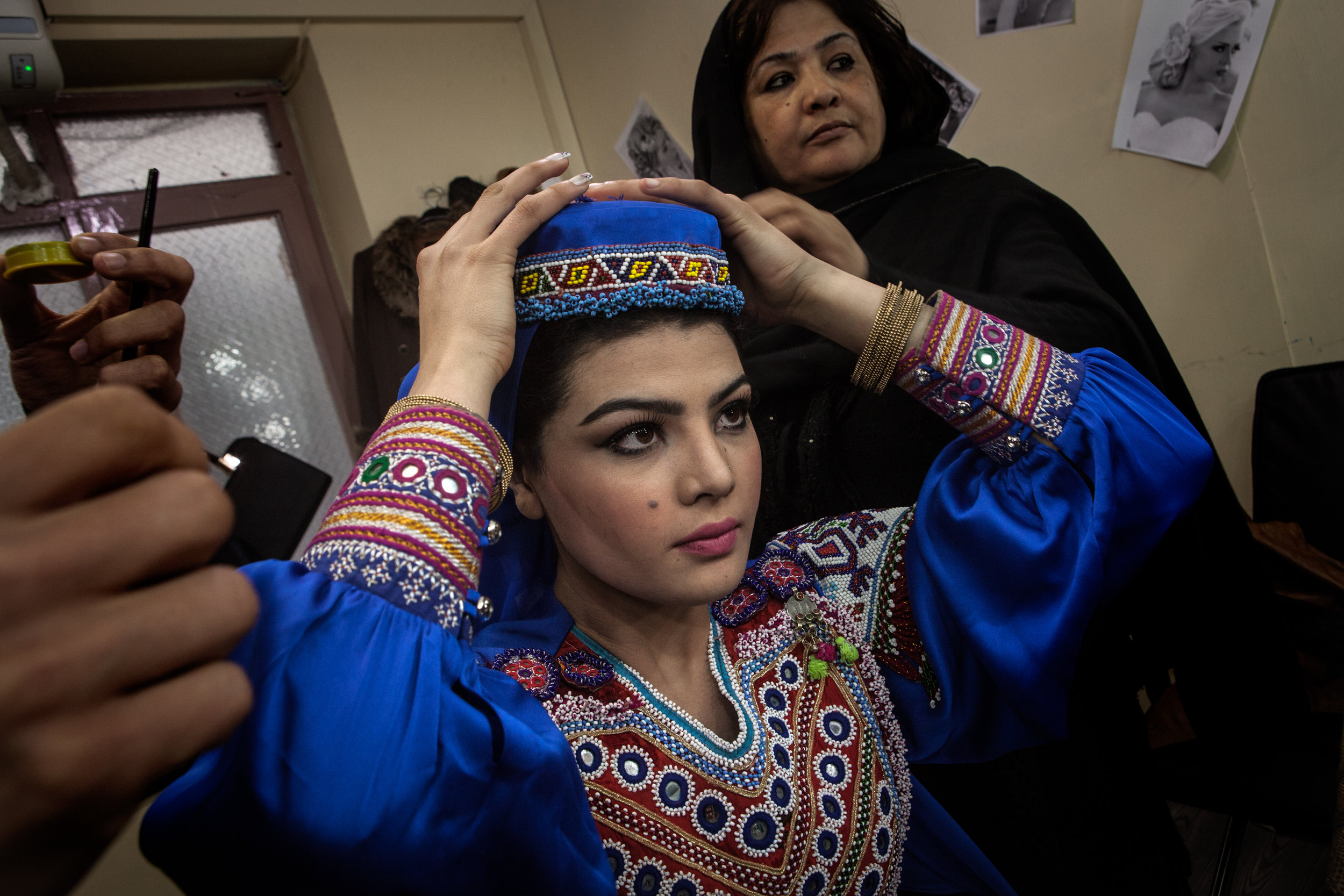"ERIN TRIEB |  www.erintrieb.com  |  @erintrieb   Zulala Hashemi, 16, is helped by her mother Mermen Hashemi as she prepares for the second round of judging on Afghan Star — a TV show similar to the U.S. show ""American Idol"" — in Kabul, Afghanistan, March 2, 2017.  [ The New York Times ]"