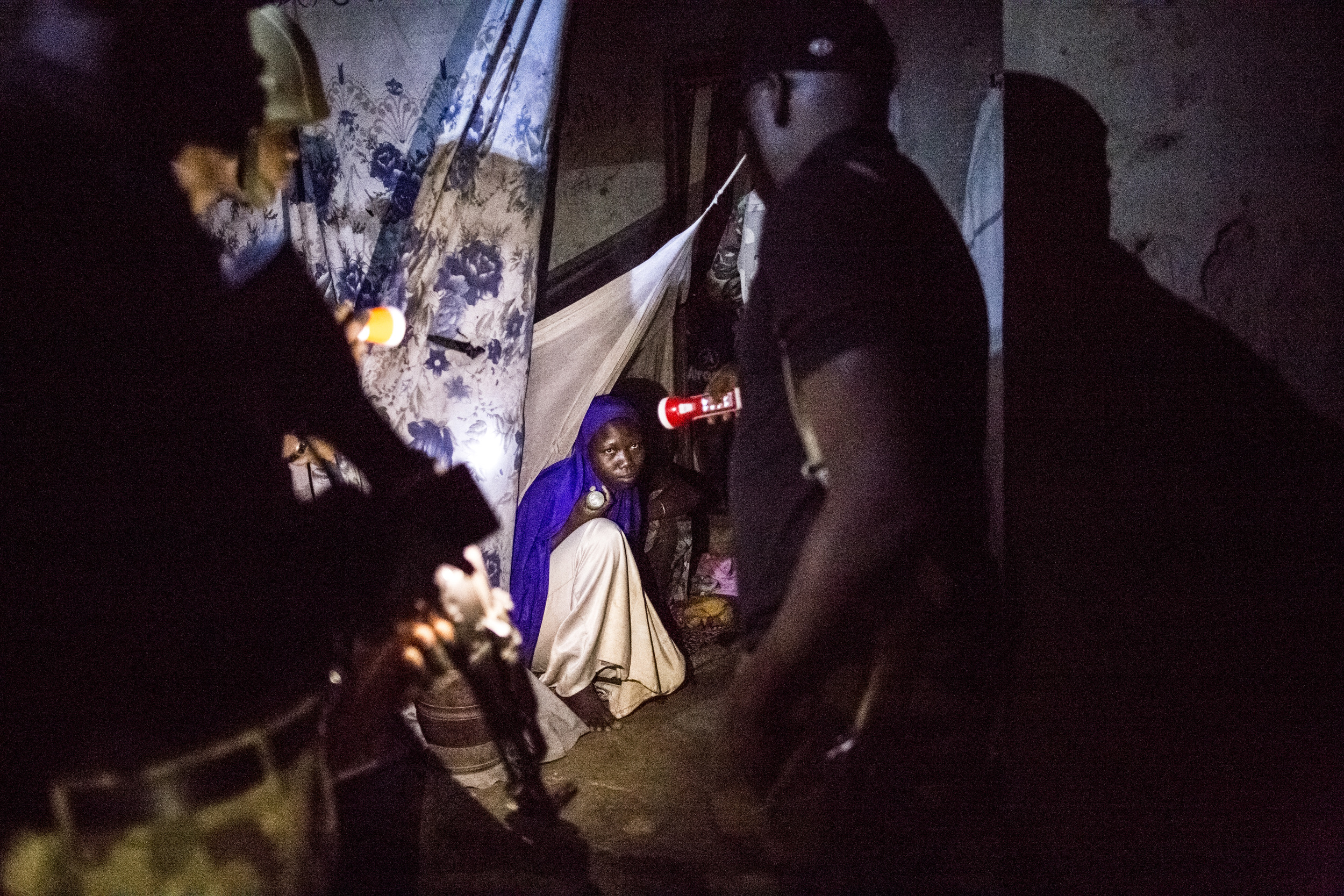 GLENNA GORDON |  www.glennagordon.com  |  @glennagordon   A young woman looks up at a solider who is checking her house for insurgents, weapons or other illicit goods during a cordon and search exercise after a suicide bombing on the outskirts of Maiduguri.   [ The New York Times Magazine ]