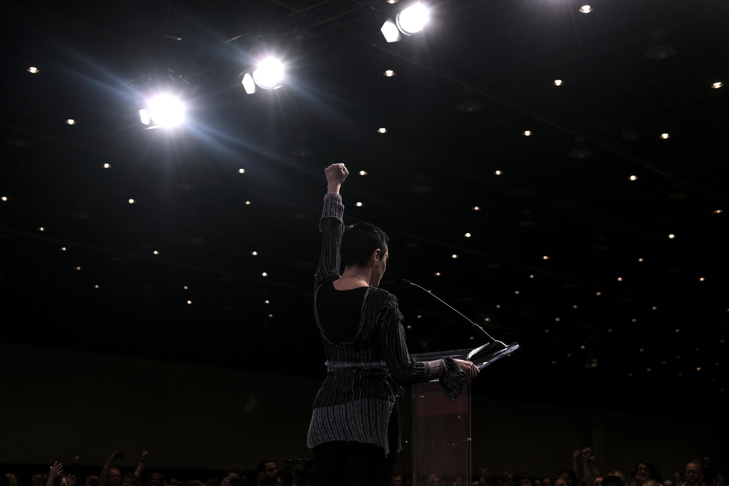 ERIN KIRKLAND |  www.erinkirklandphotography.com  |  @http://instagram.com/eakirklandphoto   Actress Rose McGowan raises her fist while delivering the opening address at the Women's Convention on October 27 in Detroit, Mich. This was the first time McGowan had spoken in public since accusing film producer Harvey Weinstein of rape.   [ The New York Times ]