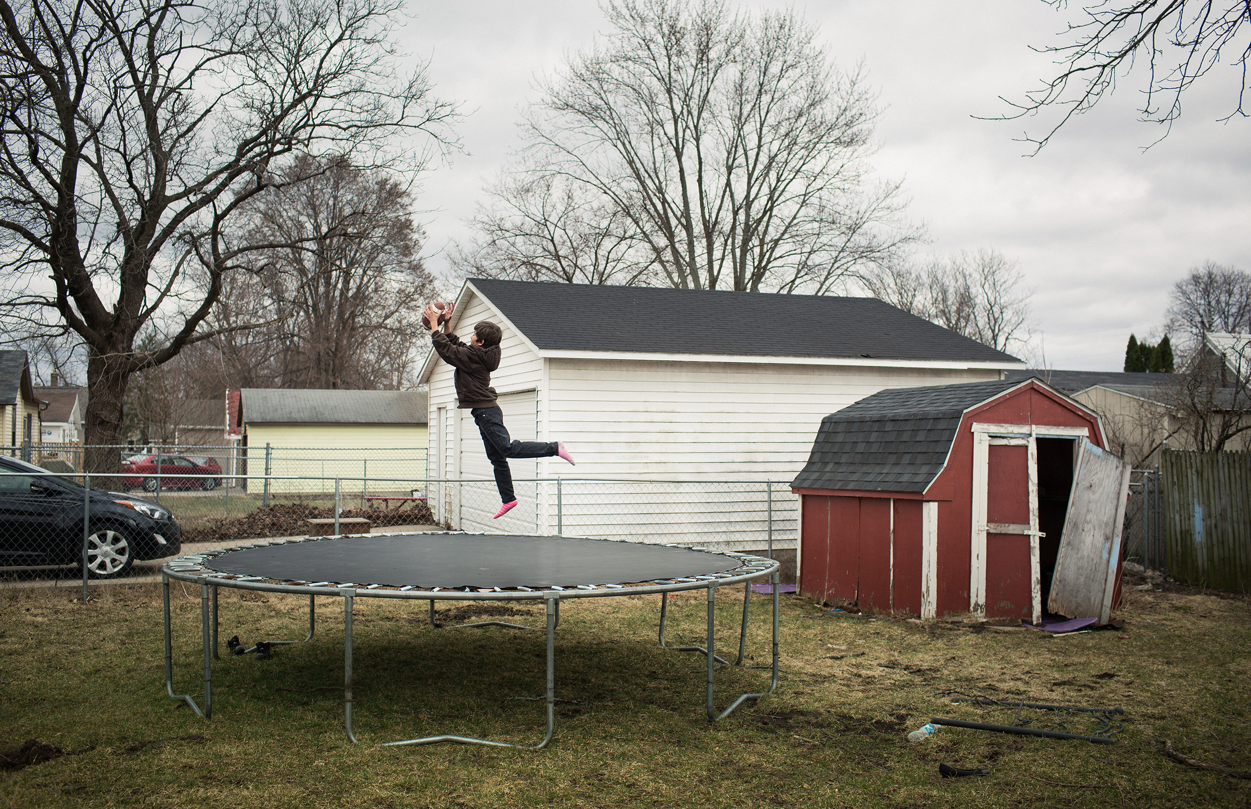 ALYSSA SCHUKAR |  www.alyssaschukar.com  |  @alyssaschukar   Karlos Denson, 9, plays an acrobatic version of football outside his home in the Fourth Ward, long one of Janesville, Wisconsin's poorer parts of town.  [ The Washington Post ]