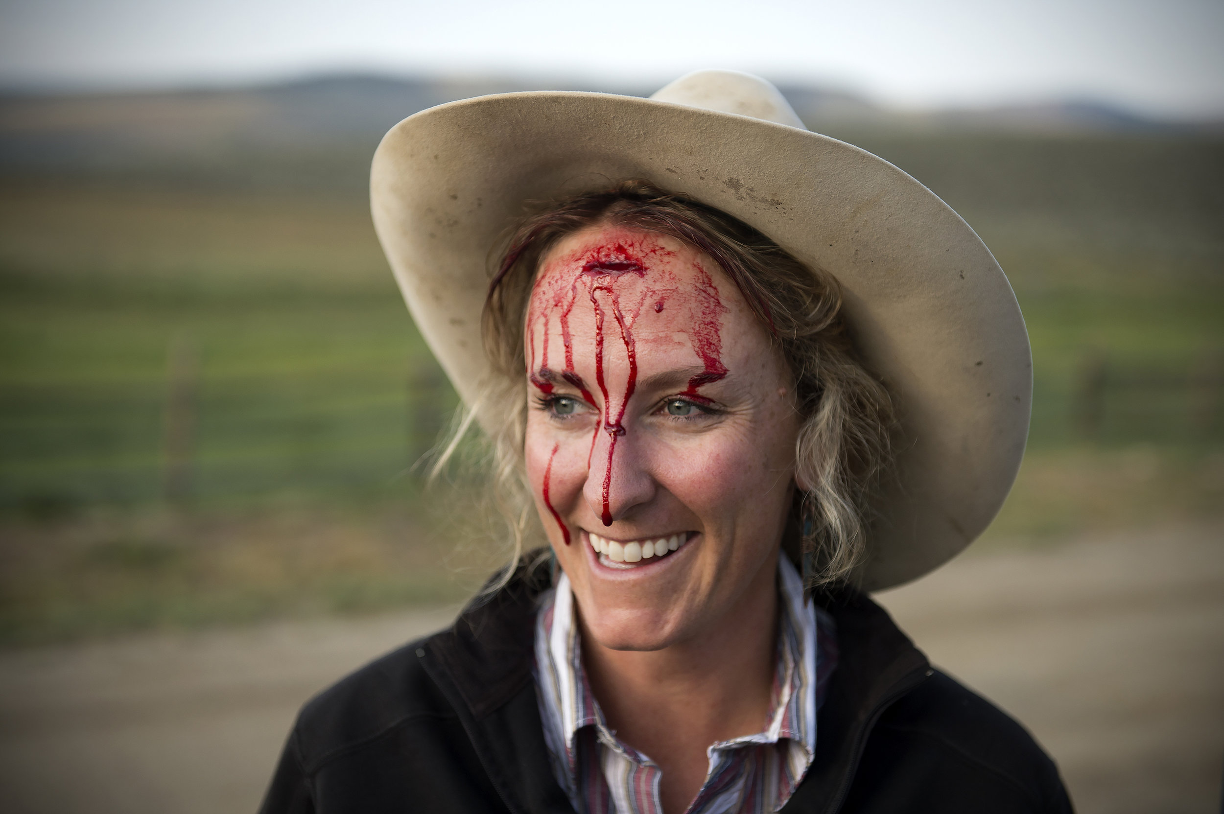 AMANDA LUCIER |  www.amandalucier.com  |  @amandalucier   Caitlyn Taussig, a rancher in Kremmling, Co., smiles as blood drips down her face after a gate hit her in the head while she was loading cattle on the ranch she runs with her mother and sister.