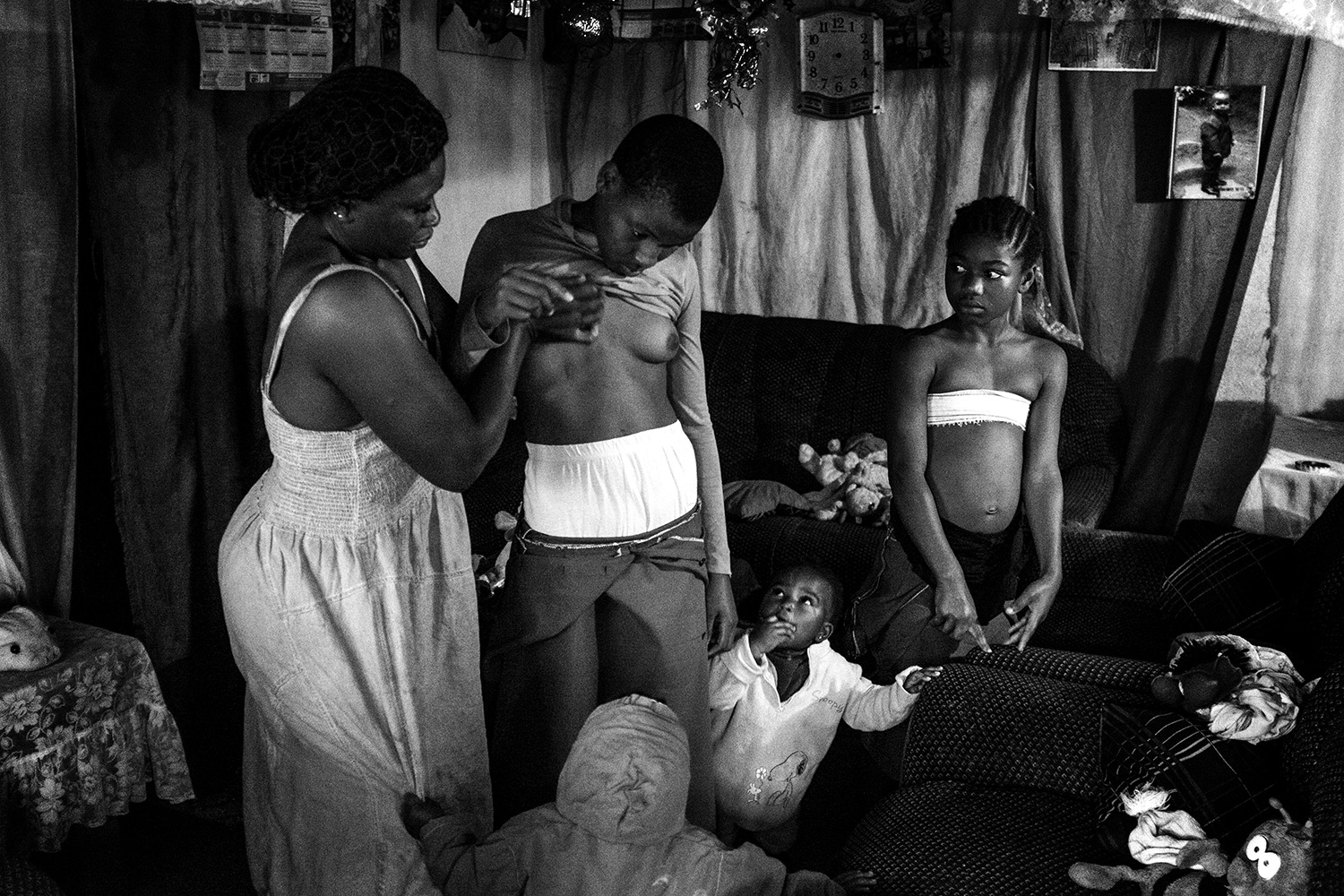From my series Banned Beauty. Veronica, 28, massages the breasts of her 10-year-old daughter, Michelle, as her other children watch. Her older daughter, not pictured, refused to have her breasts ironed and became pregnant at the age of 14. Determined to keep her younger girls from making the same mistake, Veronica ironed their breasts. This is near the city of Bafoussam in Cameroon, Africa.